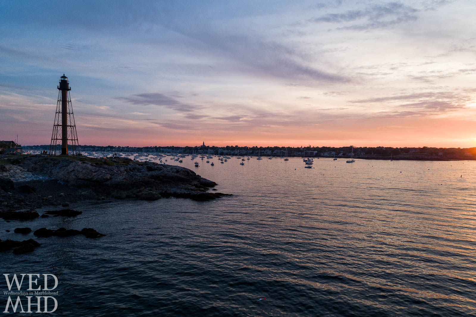 Marblehead Light marks the opening of Marblehead harbor in a low aerial view of sunset on the water