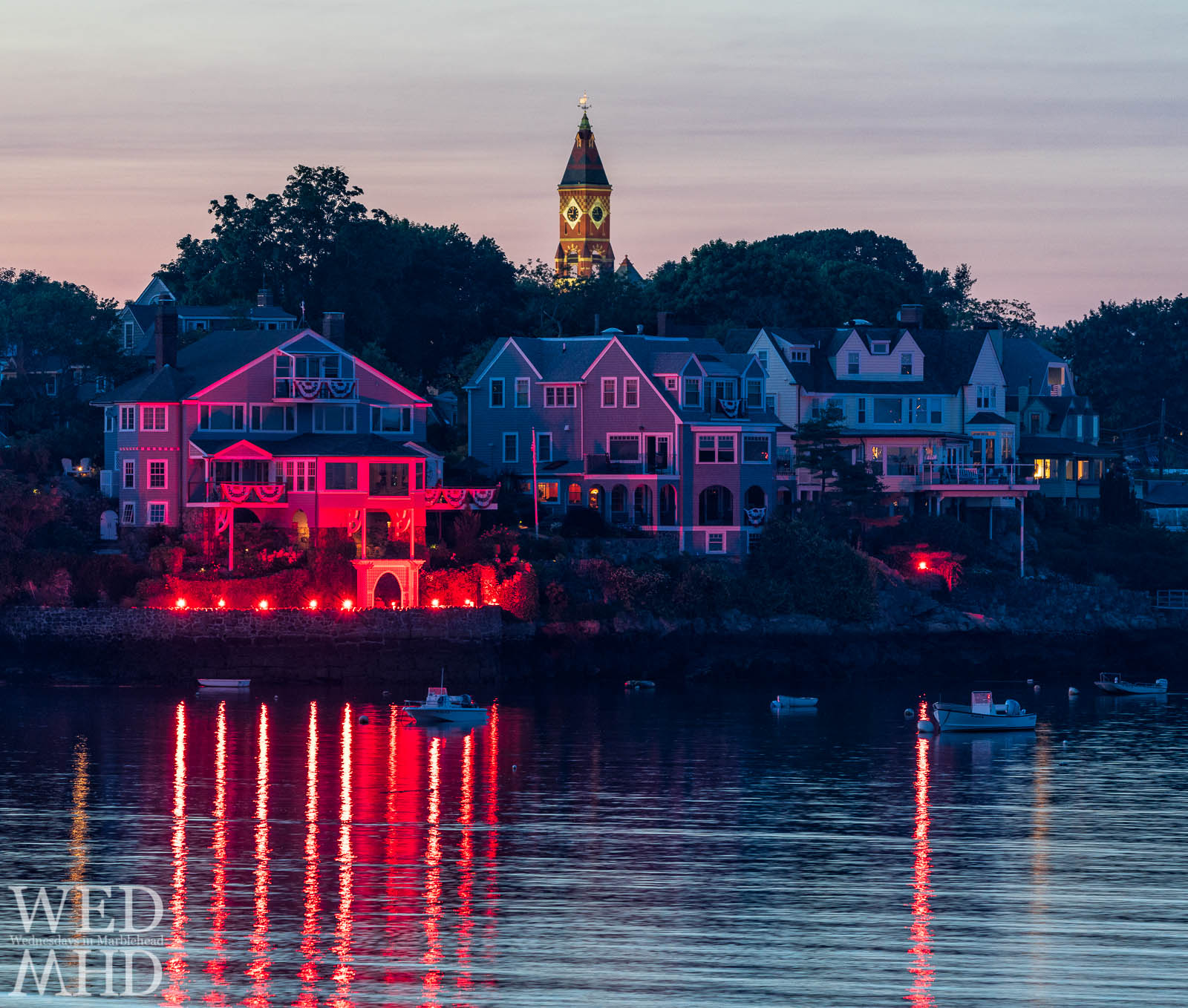 Abbot Hall stands tall over the flares circling the water during the annual harbor illumination in Marblehead