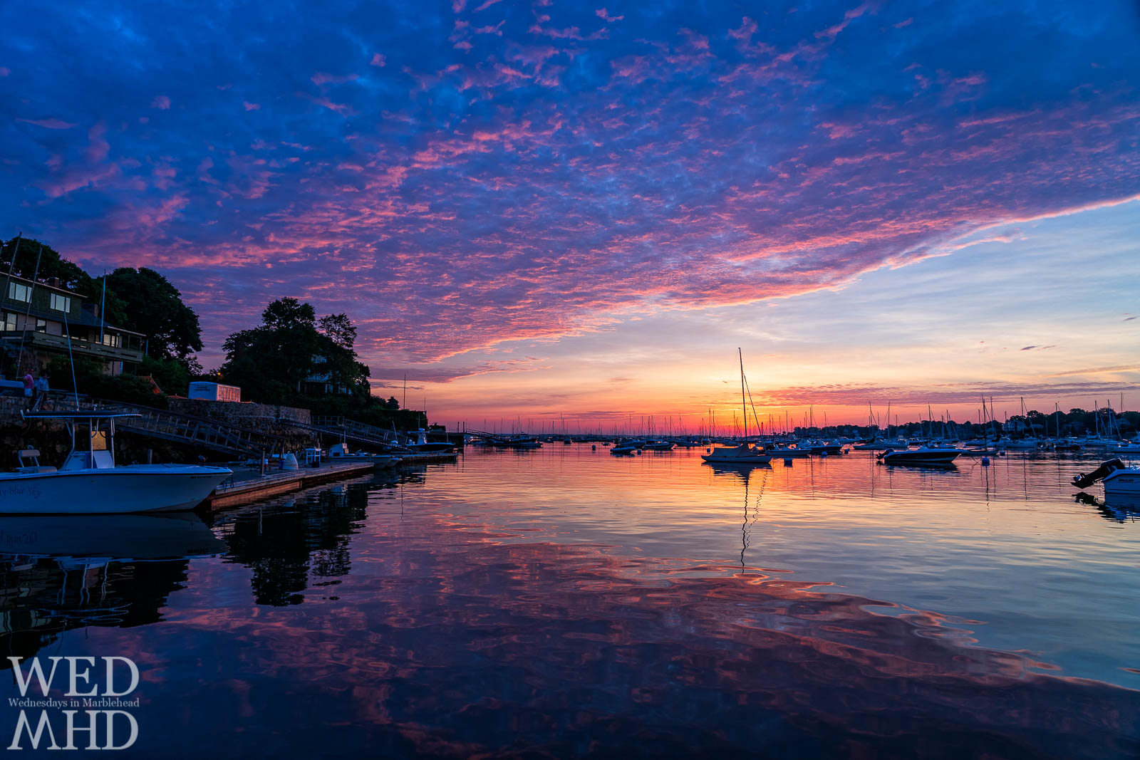 A seemingly painted sunrise is perfectly reflected in the still water of Marblehead Harbor with a boat named Blue Sky perfectly positioned in frame