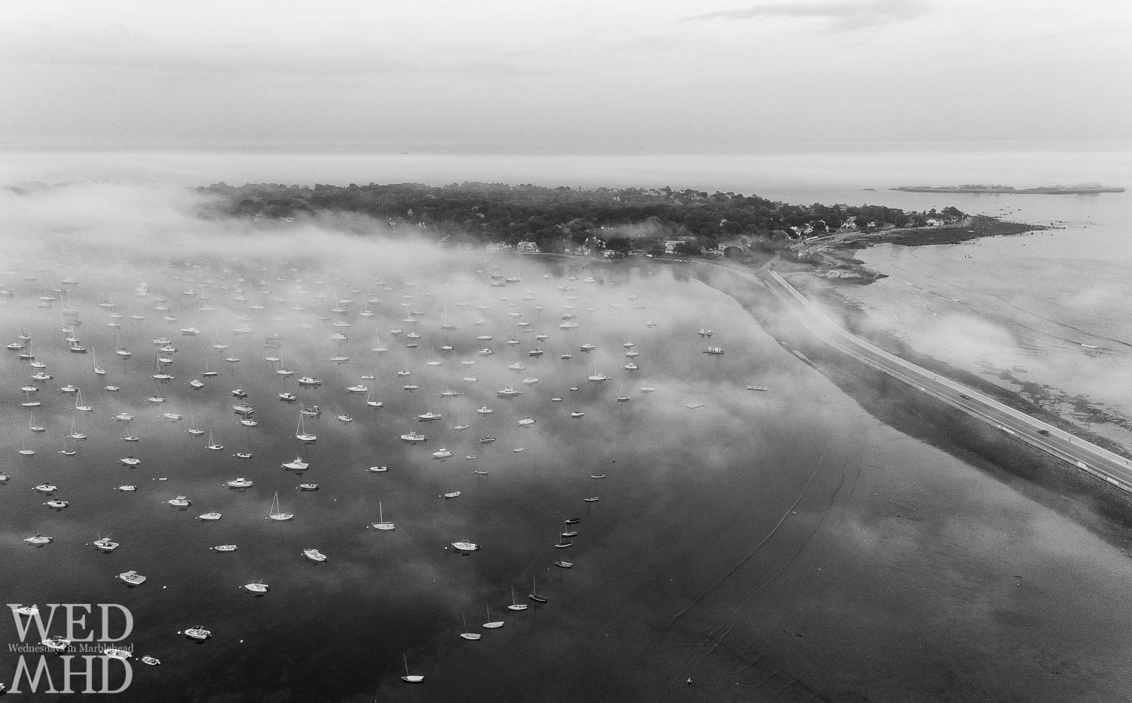 Flying high abover Riverhead Beach reveals this view of fog on the harbor filled with boats and the Neck stretching out beyond
