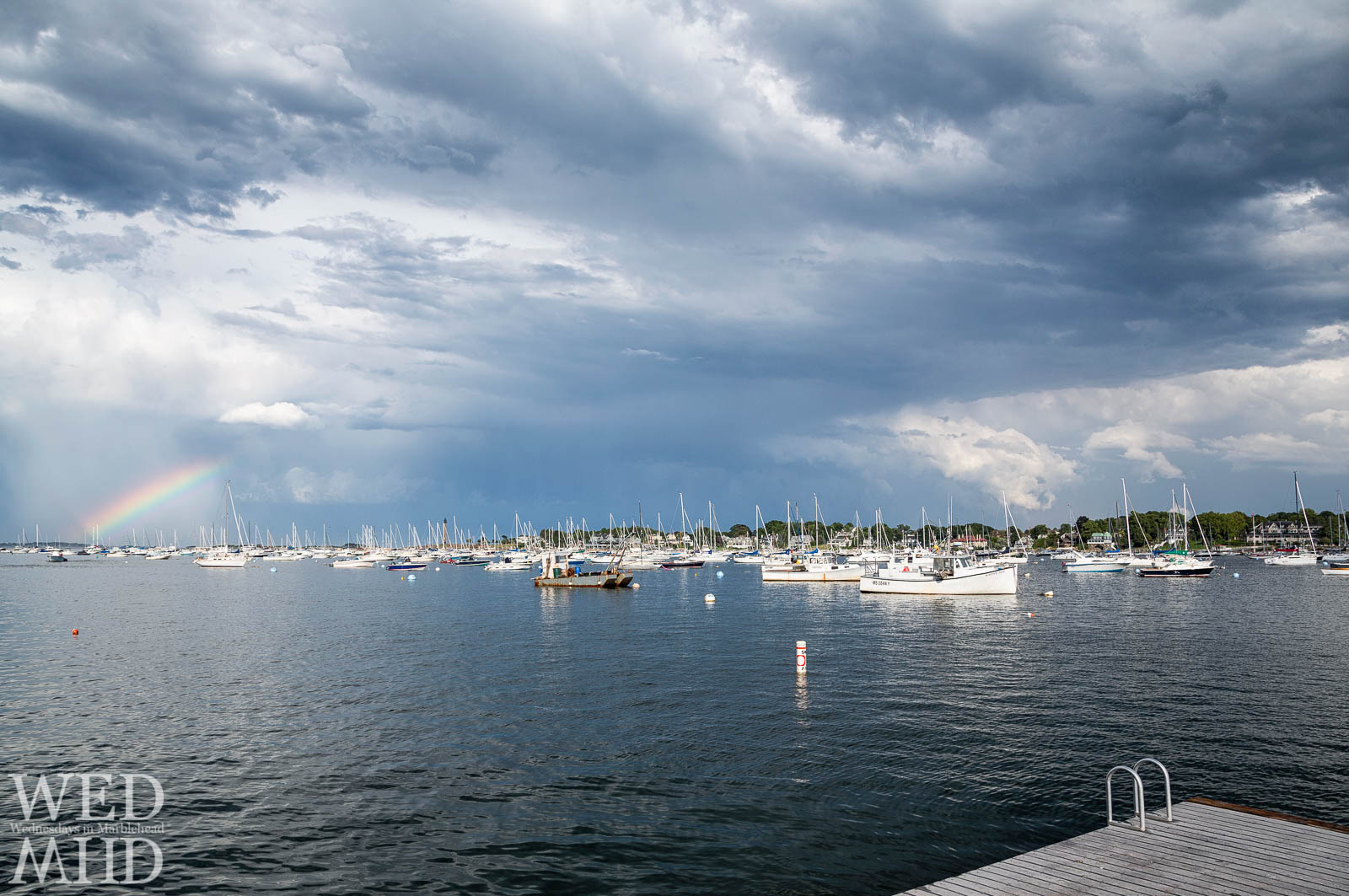 A rainbow appears over a full Marblehead Harbor as seen from the float at Crocker Park