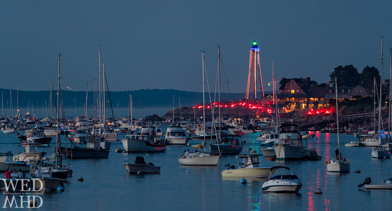 Flares light up the harbor and reflect in the still water on the Fourth of July displaying the magical illumination that occurs annually before the fireworks show
