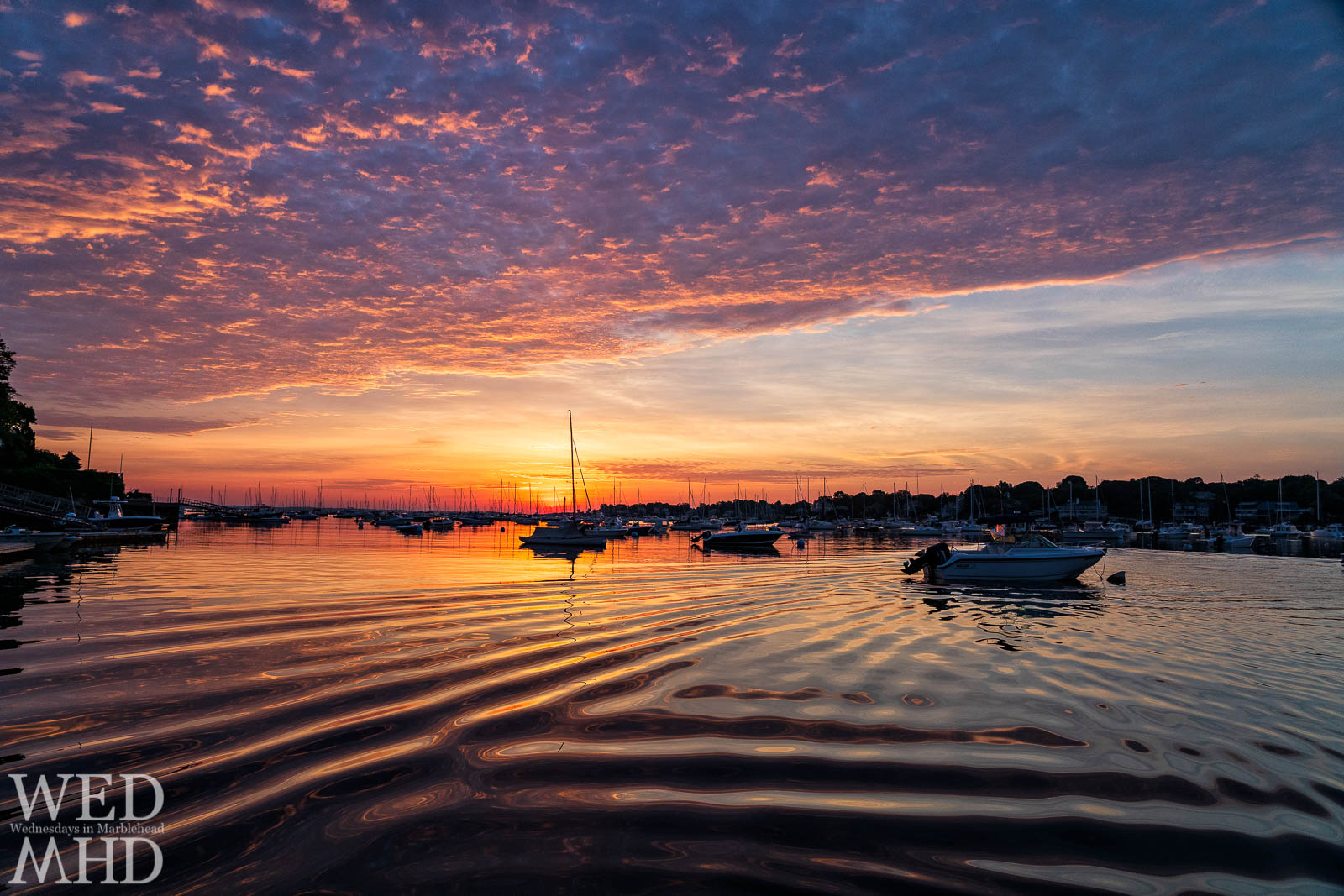 A passing boat's wake creates subtle waves to accentuate sunrise reflections on Marblehead Harbor