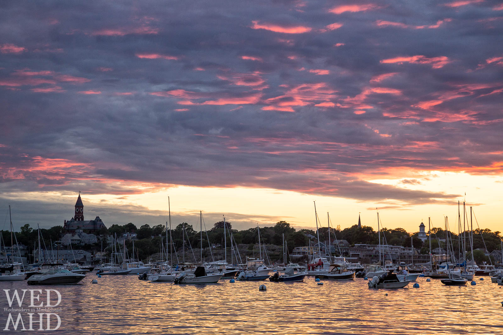 Boats are stacked up for sunset between Abbot Hall and Grace Community Church with a pink sky above and golden light on the water