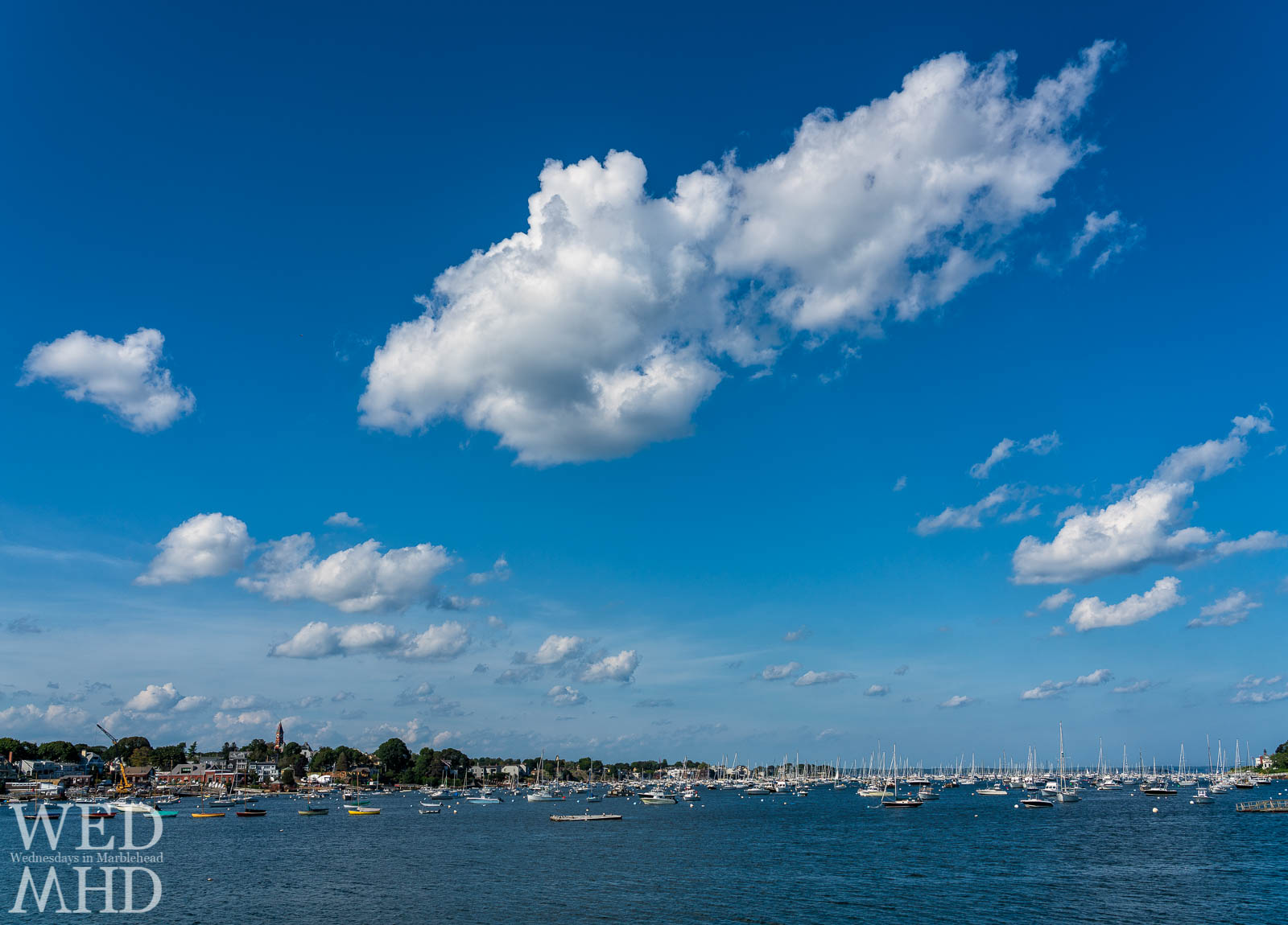 Blue sky punctuated by white clouds rise over Marblehead Harbor on a hot summer day