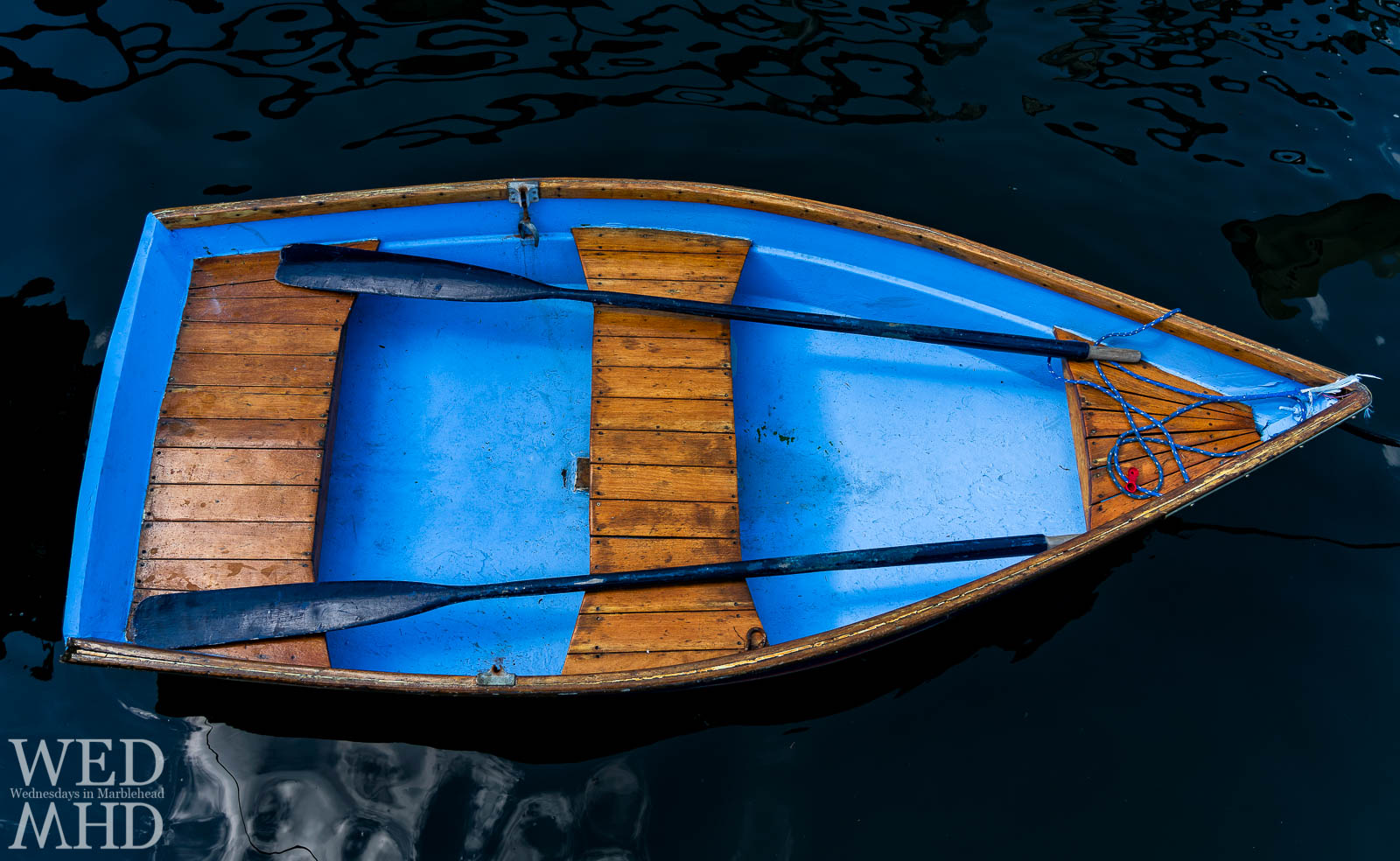 A small blue dinghy is moored in Little Harbor