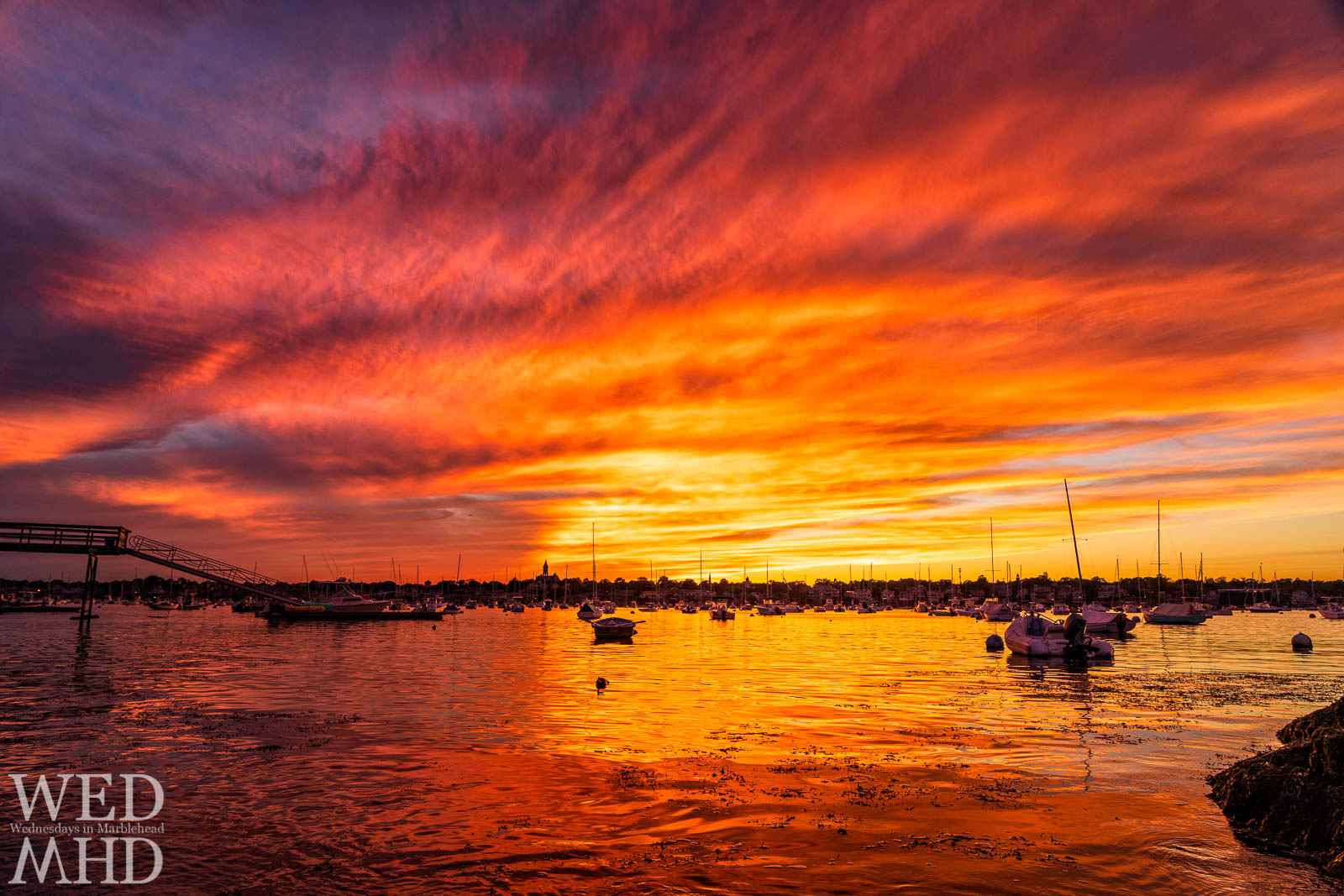 A late September sunset creates epic light from Peabody Lane with brilliant orange reflections on the waters of Marblehead harbor