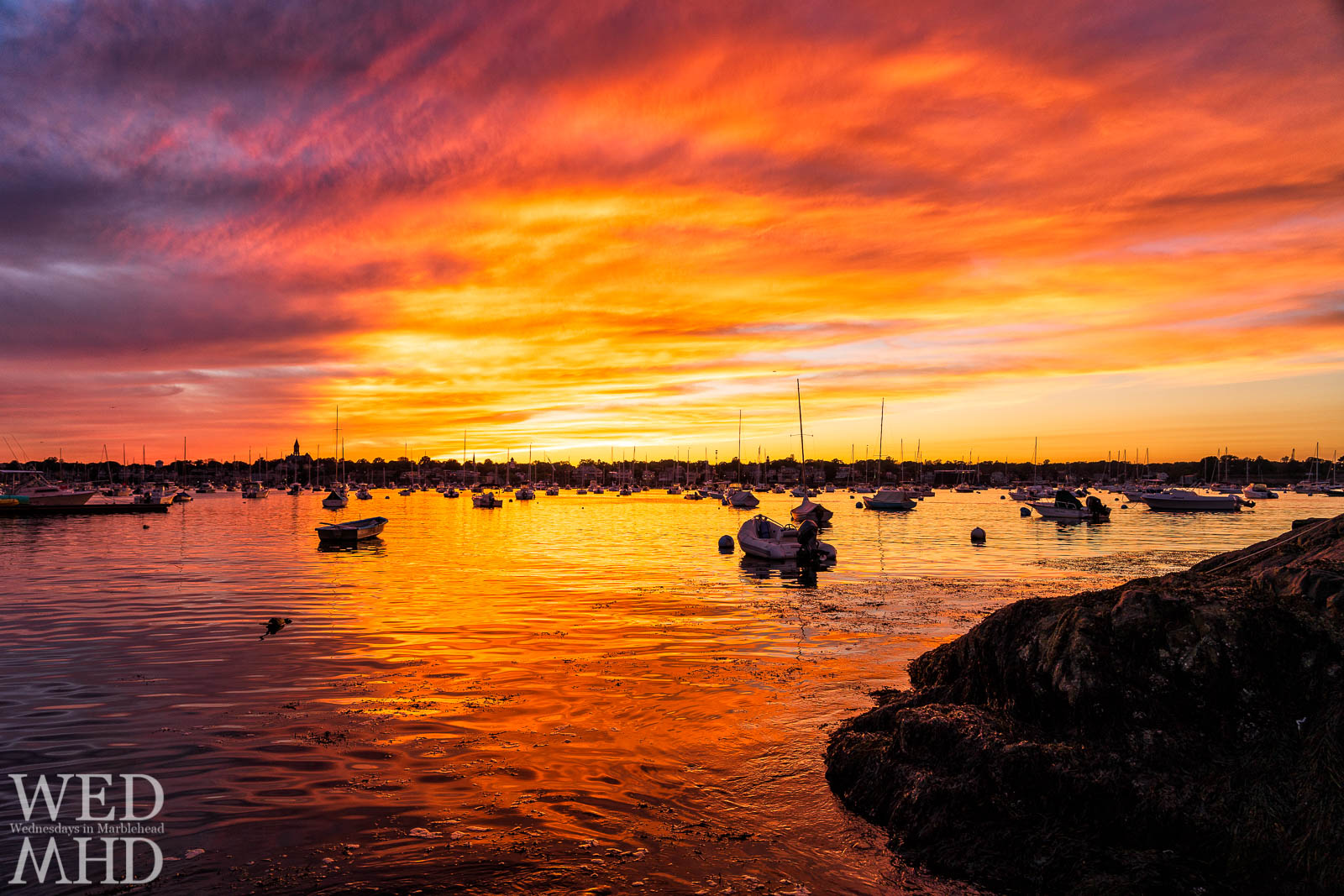 Sunset erupts in an explosion of light over Marblehead Harbor and paints the water in an orange glow
