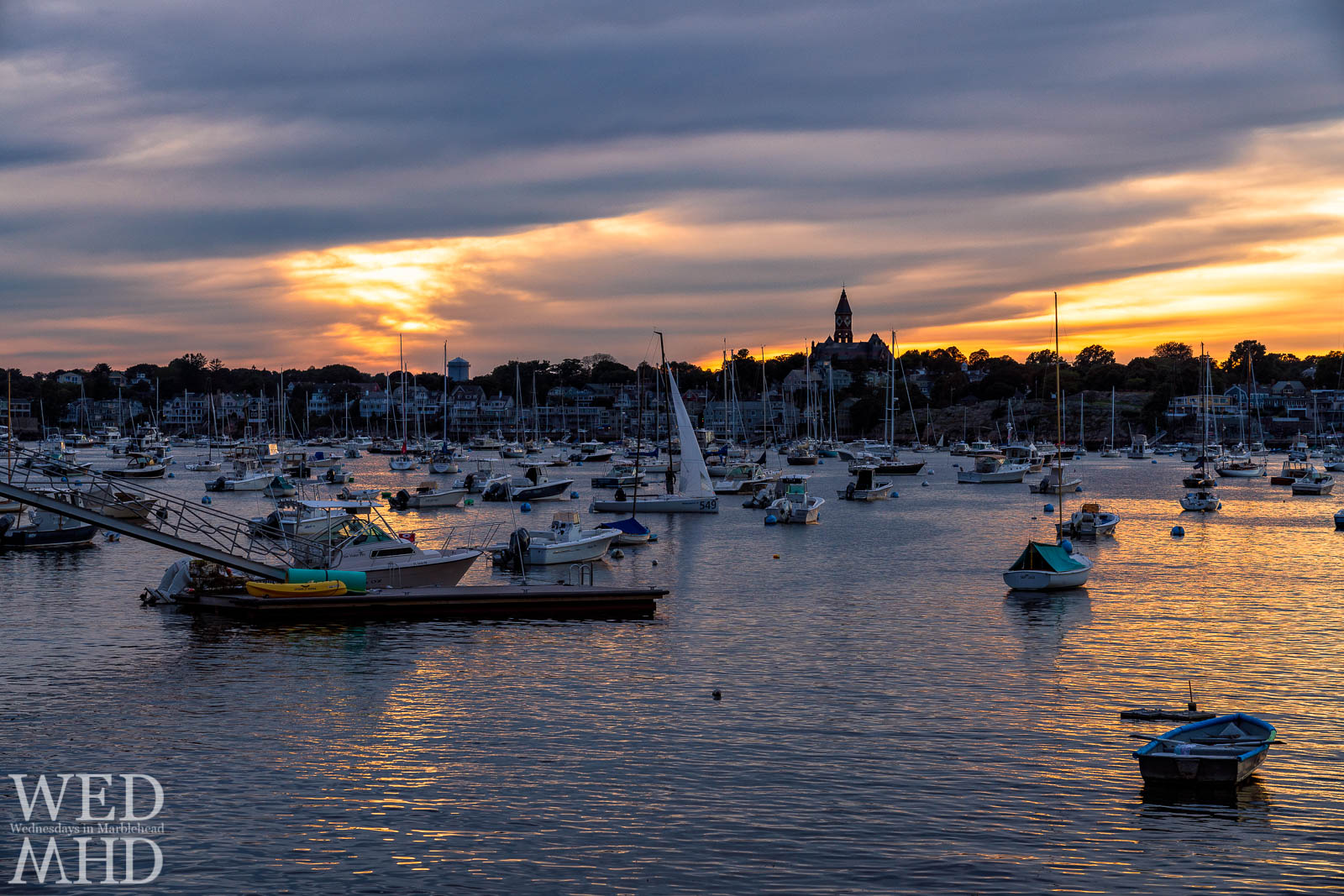 A lone J70 glides through Marblehead Harbor before the start of the J70 World Championship
