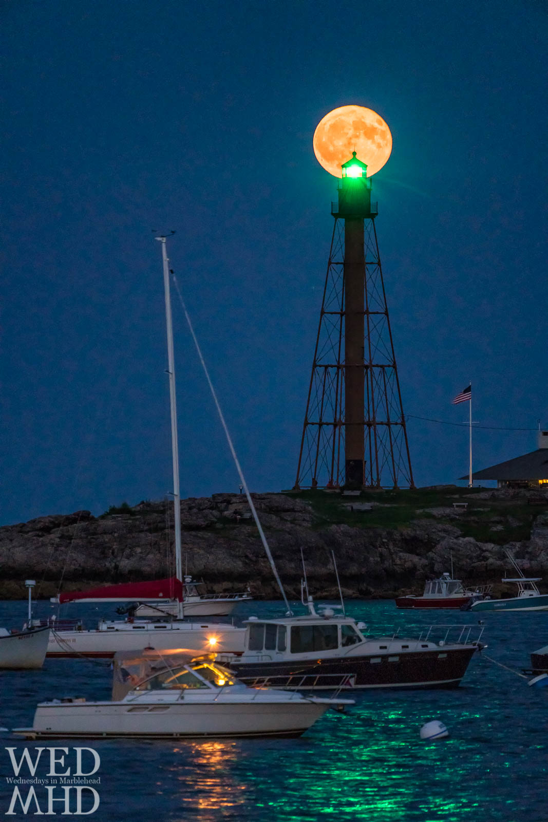 The full moon rises directly behind Marblehead Light on a late August evening with boats in the harbor and a flag waving in the night sky