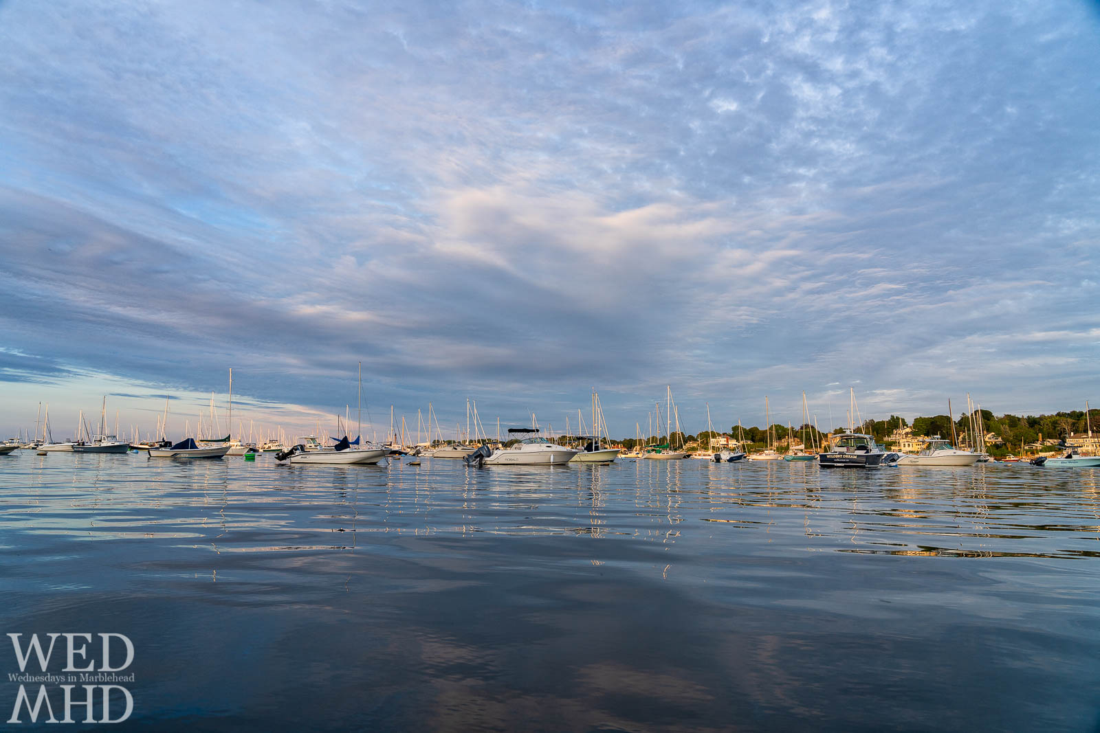 The still water of Marblehead Harbor creates perfect reflections of boats and their masts under a partly cloudy sky just before sunset on a September evening