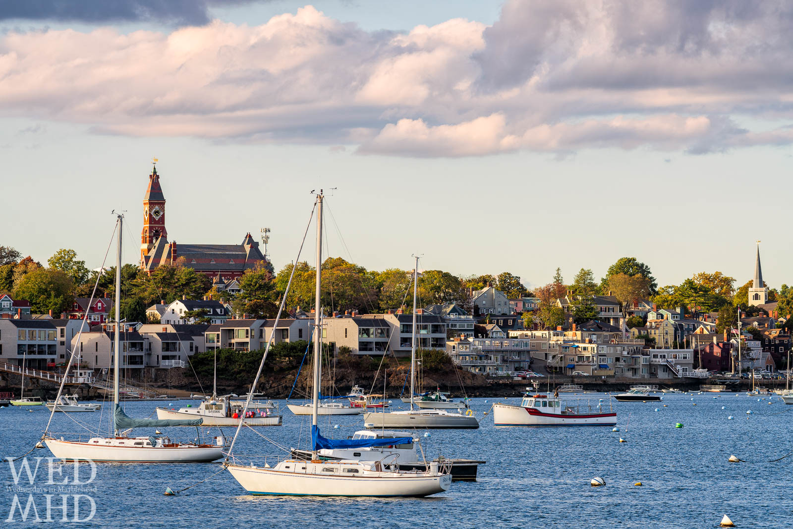 Fewer boats fill their moorings as fall takes hold in Marblehead Harbor. Subtle foliage can be seen across the harbor.