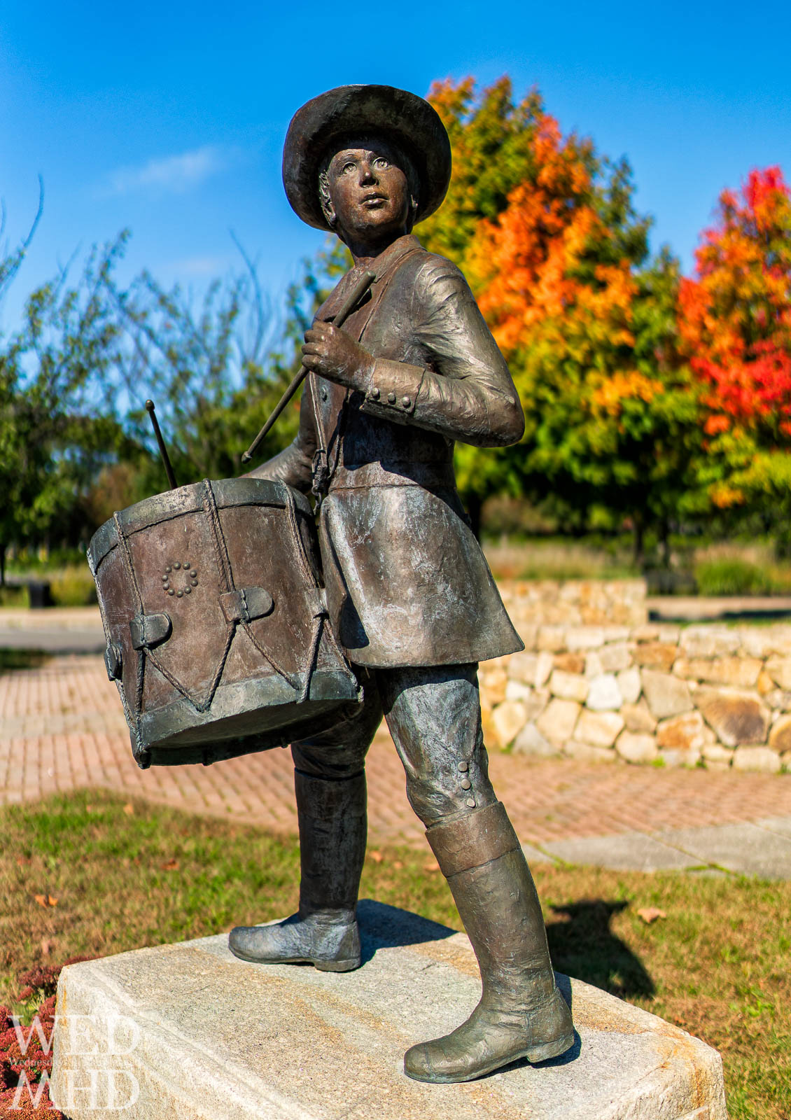 A sculpture of the little drummer boy stands at Marblehead High School on a bright Fall day with foliage as backdrop