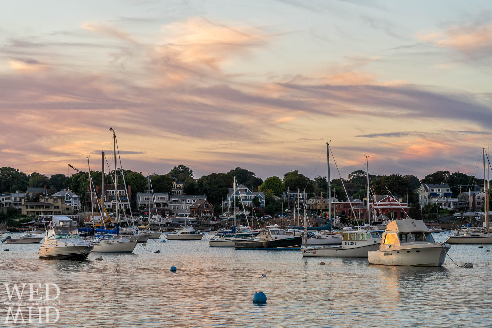 Sunset is reflected in the windows of a boat moored mid-harbor as the moorings begin to empty with the calendar turning to October