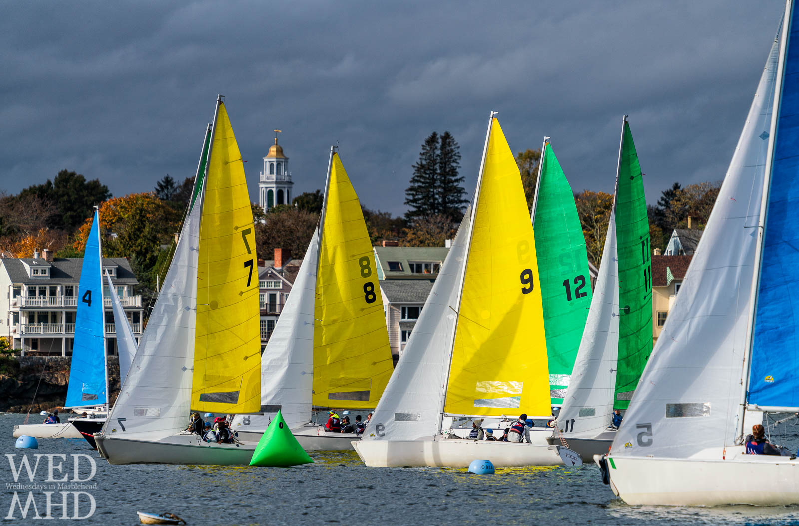 The annual Halloween Race takes place inside Marblehead Harbor with colorful sailboats racing neck and neck past familiar landmarks like Old North Church