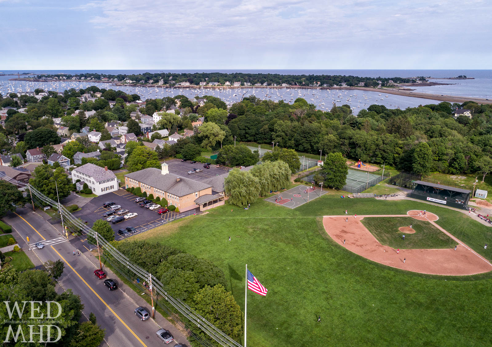Aerial view of the Seasiders playing ball at Seaside Park with a filled harbor and Marblehead Neck serving as a perfect backdrop