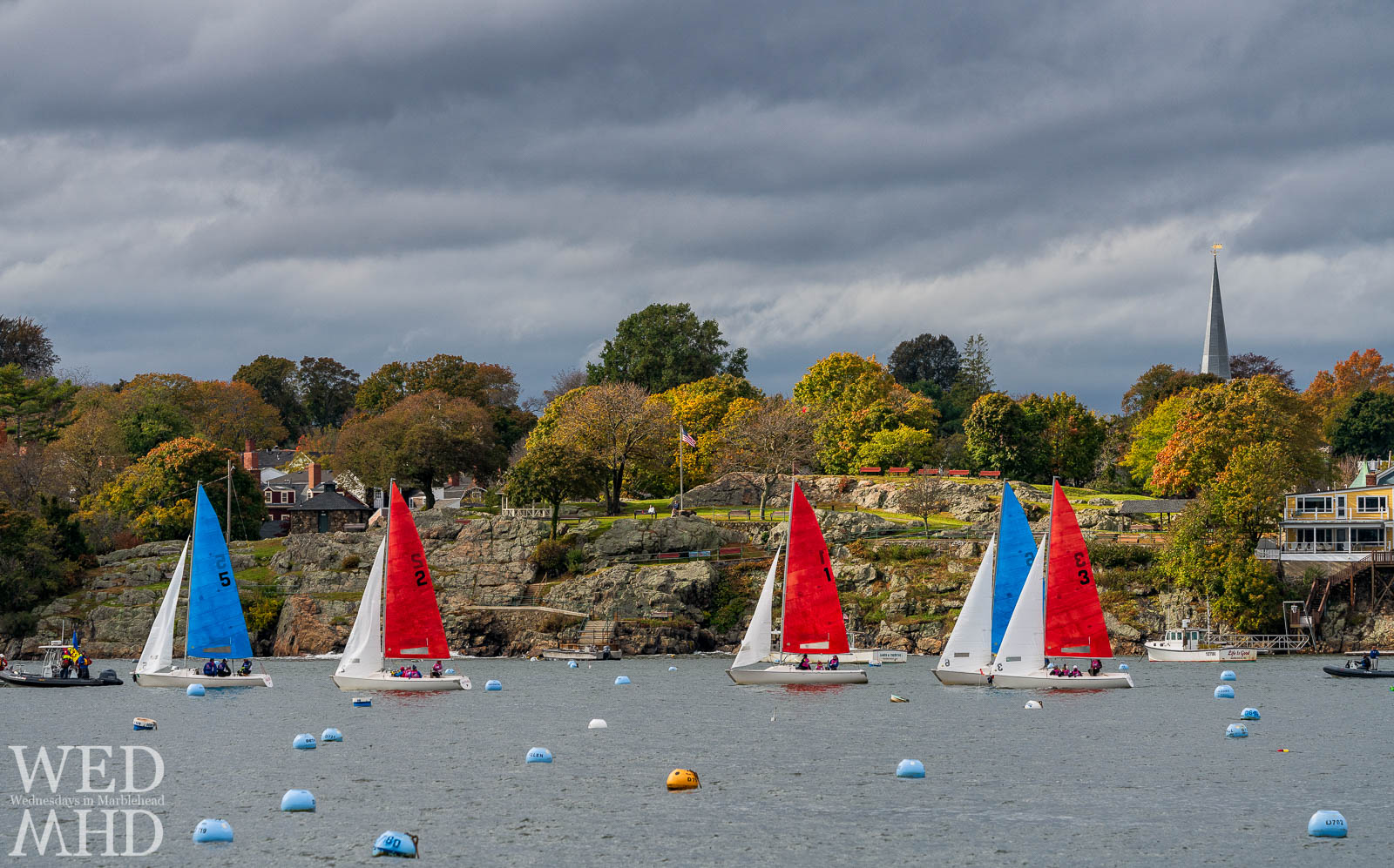Halloween racing takes place in Marblehead Harbor on a fall day with hints of foliage showing beyond the coloful boats