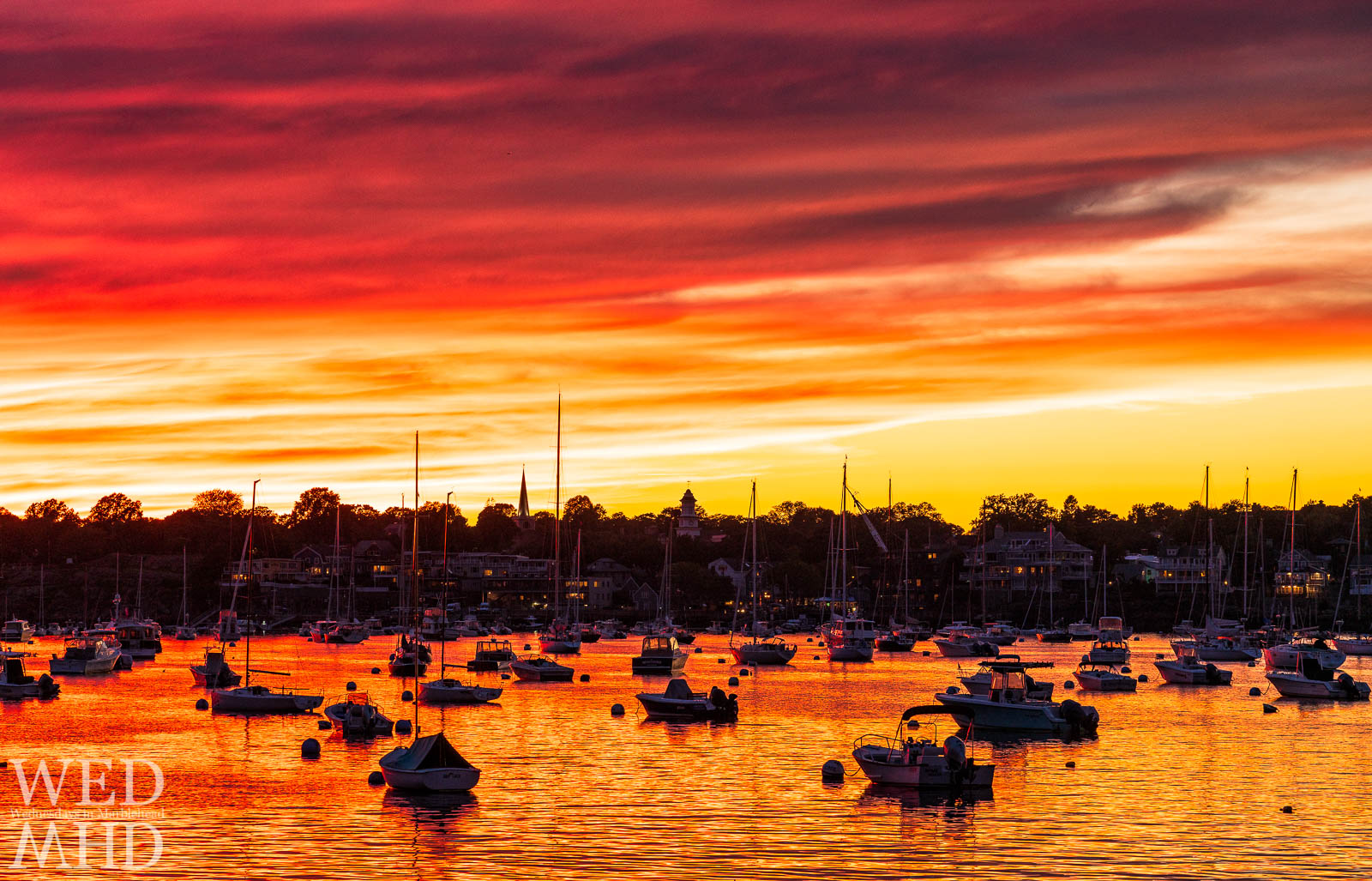 The red glow of sunset reflects in the waters of Marblehead Harbor with views of St. Michael's steeple and Grace Community Church punctuating the skyline