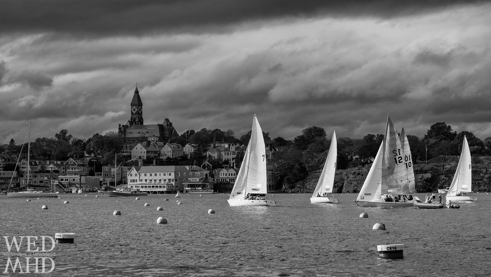 Boats are caught in a patch of sunlight setting sail toward Abbot Hall in this black and white image of the annual EYC Halloween Race