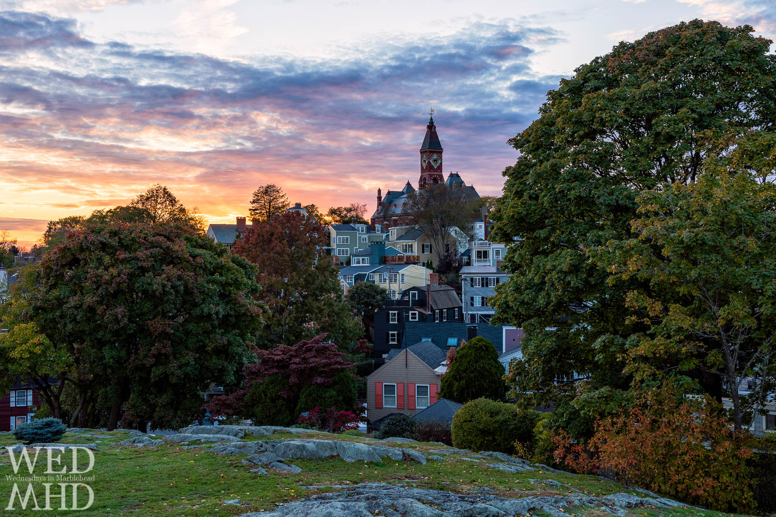 Brilliant sunset colors complement foliage in the trees of Crocker Park with Abbot Hall and houses filling the frame