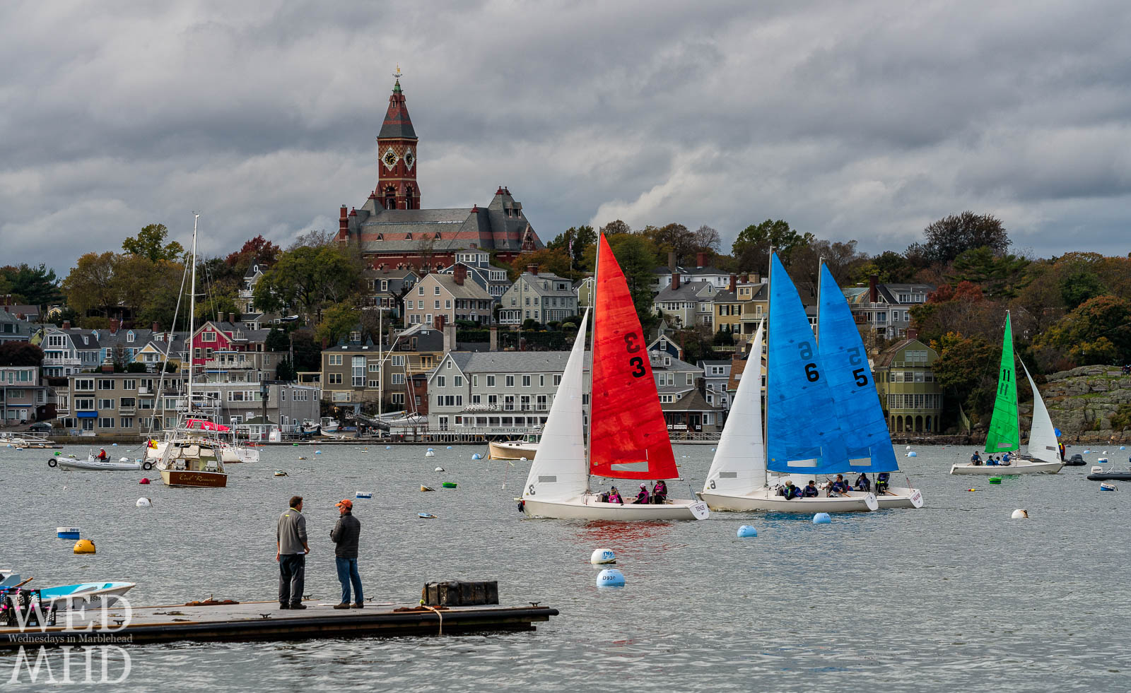 Spectators watch as the boats pass by Abbot Hall during the annual Halloween race in Marblehead Harbor