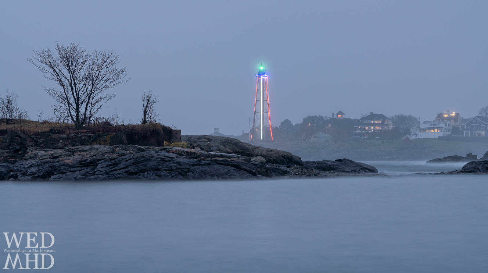 Marblehead Lighthouse stands as a beacon of light in the fog on an early December evening with strings of lights adding to the glow of the lighthouse