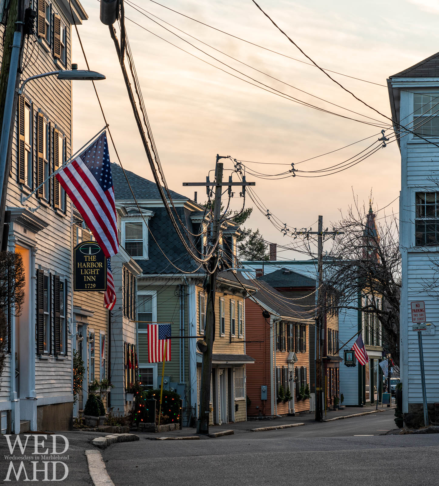 Four flags decorate homes and businesses along Washington Street as the sun sets on an early December evening in Marblehead