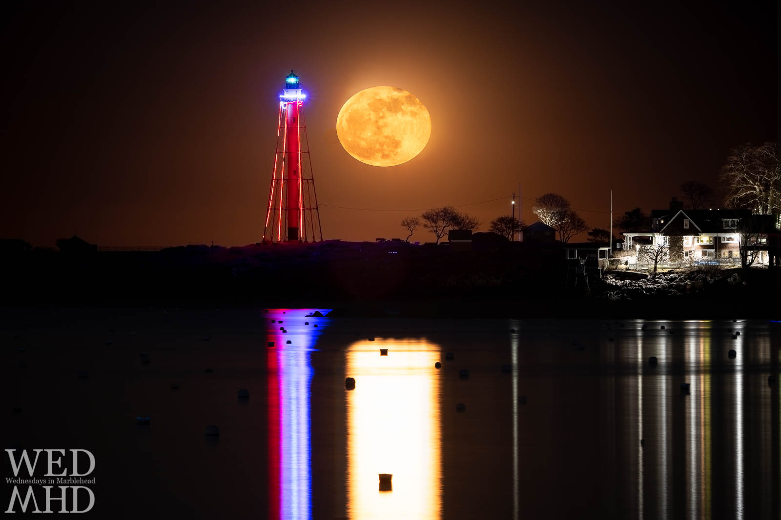 The full cold moon rises next to Marblehead Light creating a moonlit reflection in the still waters of Marblehead Harbor