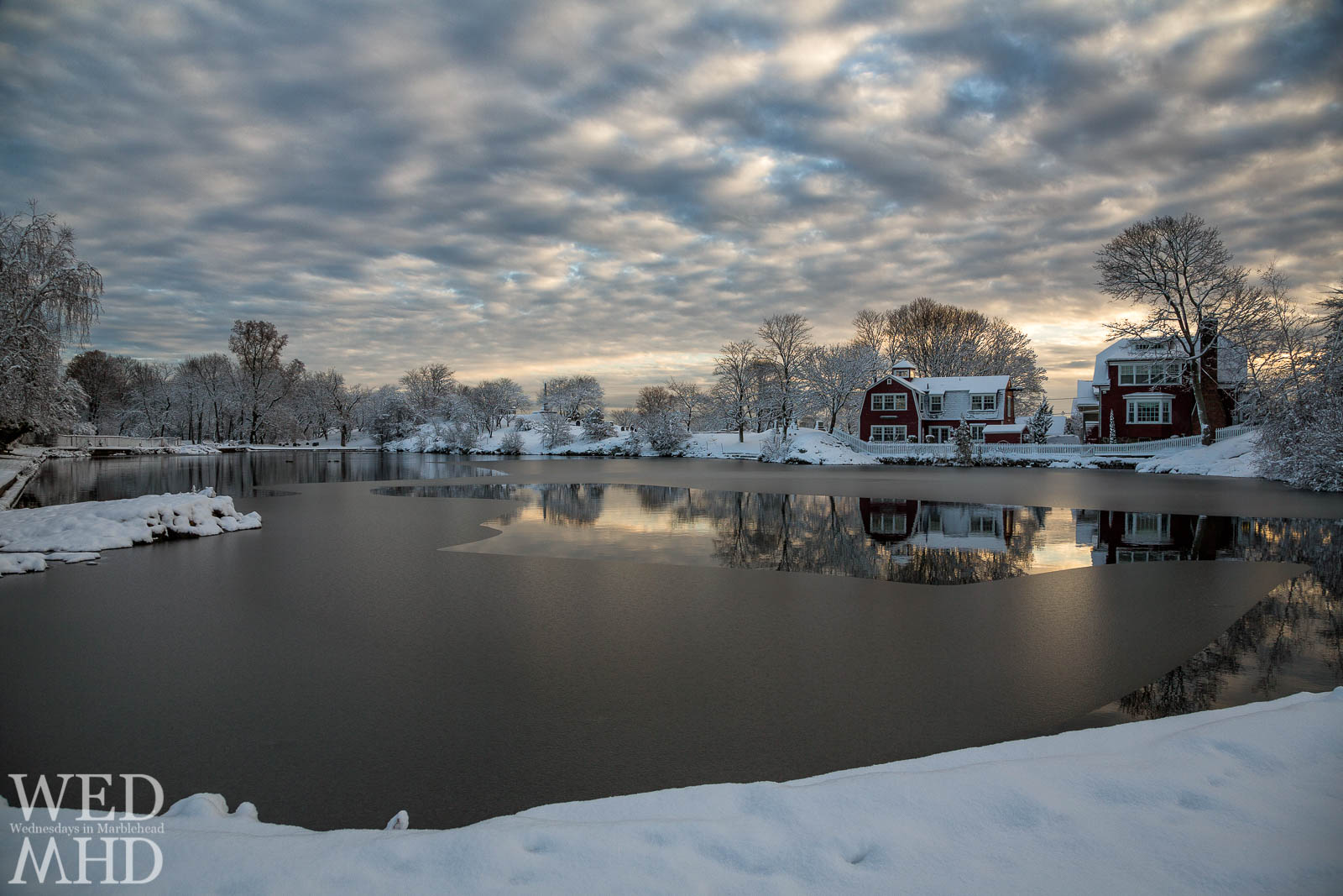 The sun rises over Redd's Pond which has begun to freeze after the first snowfall of the season