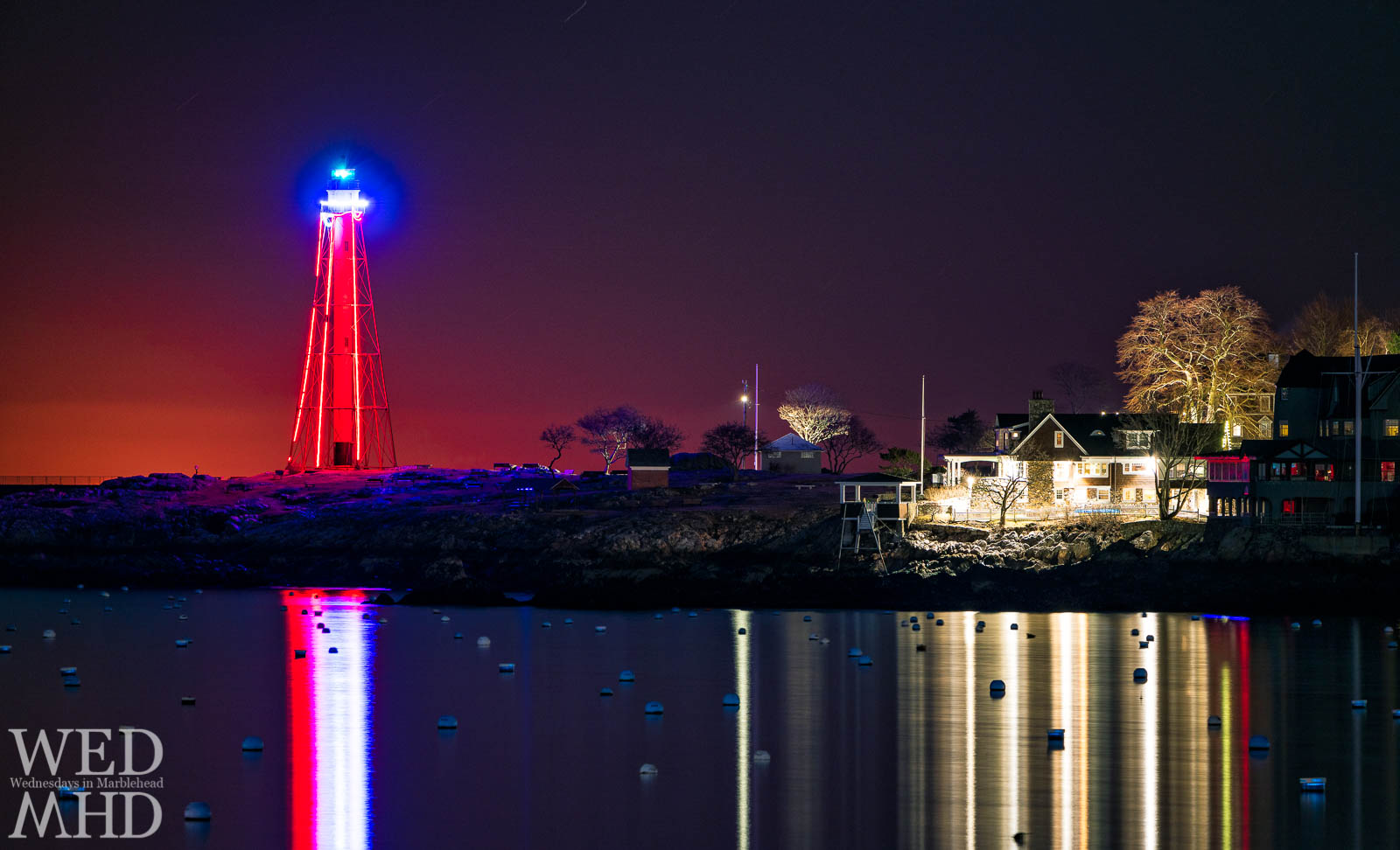Marblehead Light appears as a shining red beacon in the night illuminated by the lights draped across its iron frame