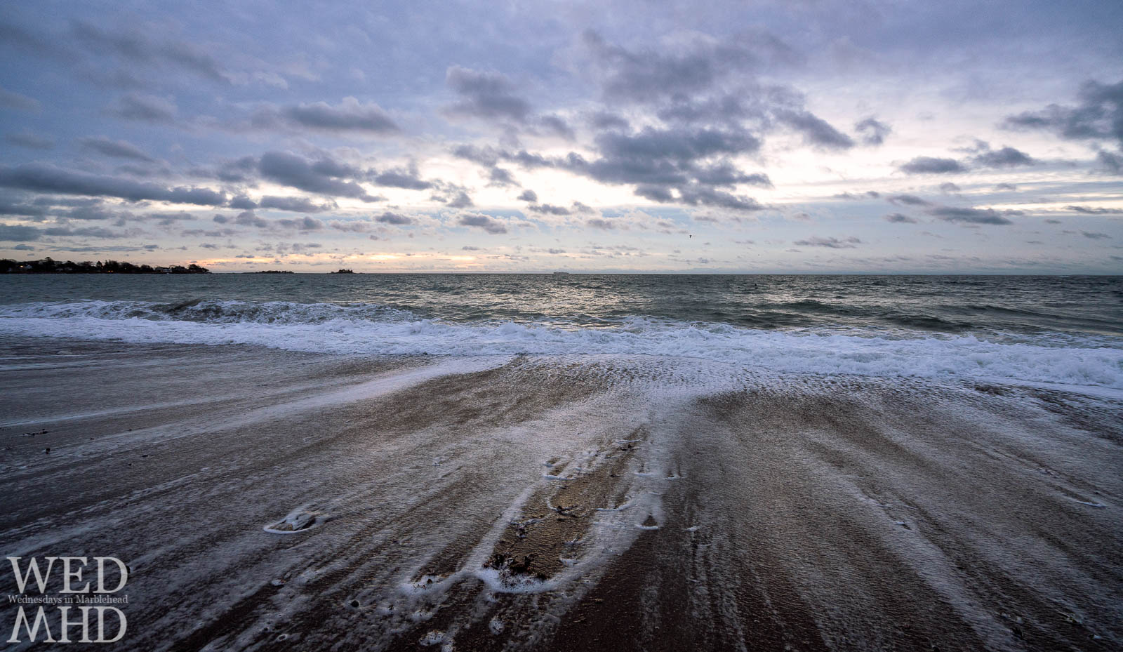 Waves recede at Devereux Beach illustrating the pull of the ocean as a new day dawns in Marblehead
