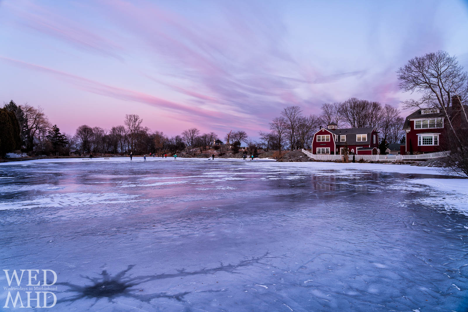 Adults and children gather on the ice at Redd's Pond for a sunset skate on a cold day in February