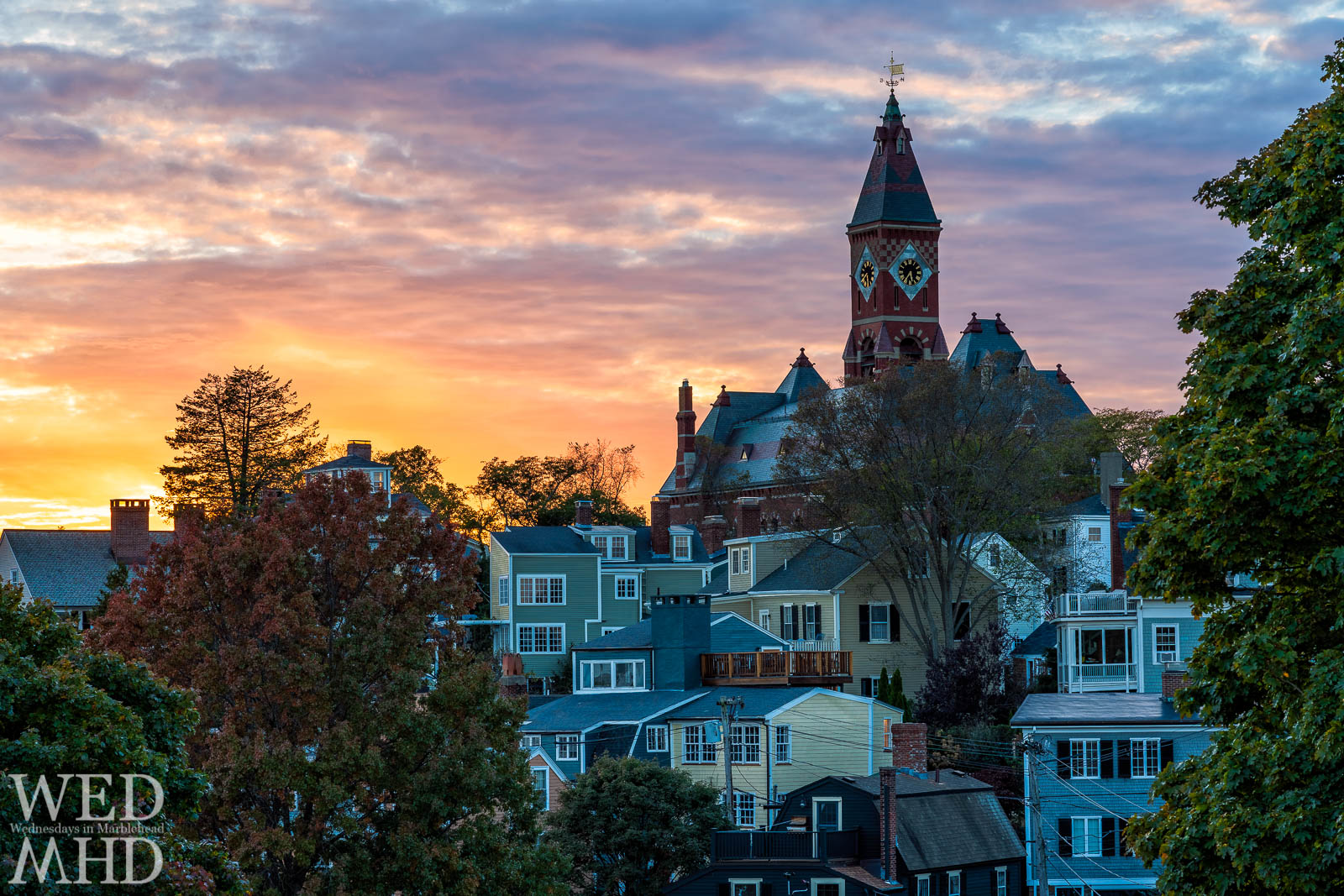 Abbot Hall stands above houses and under a brilliant sky viewed from Crocker Park at sunset