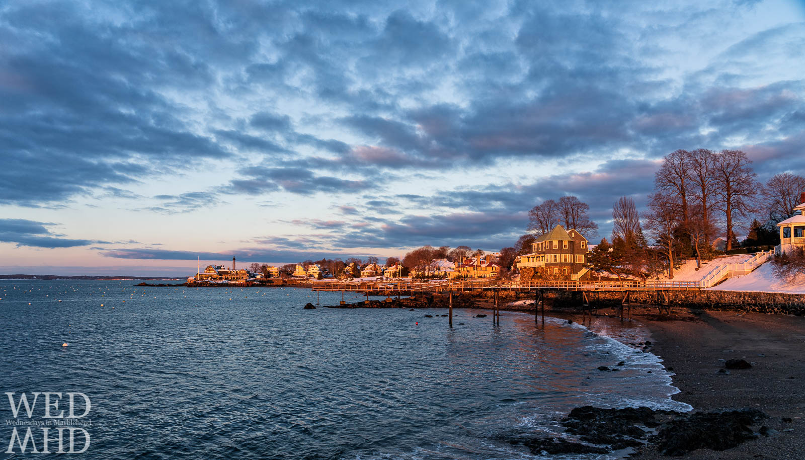 Stately homes and the Corinthian Yacht Club are glowing on the neck as the sun dips in the sky on a winter evening in Marblehead