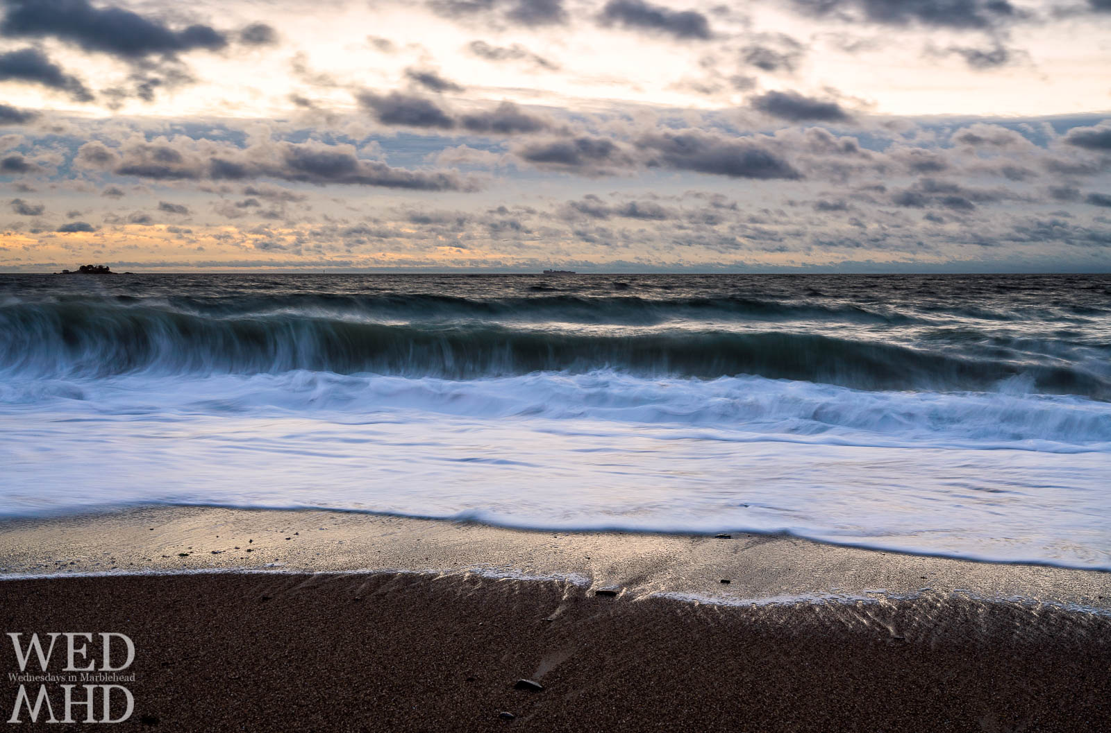 A long exposure captures the arc of an ocean wave coming ashore at Devereux Beach on New Years Day