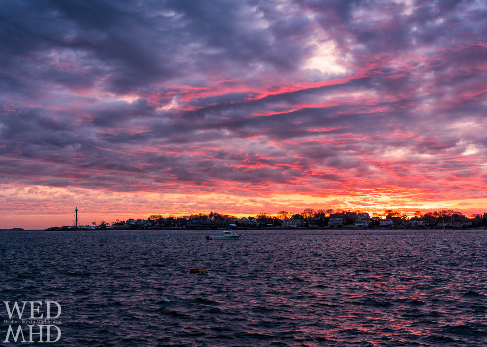 A brilliant sunrise paints the sky in pink and orange over a purple harbor with Marblehead Light's green beacon shining bright