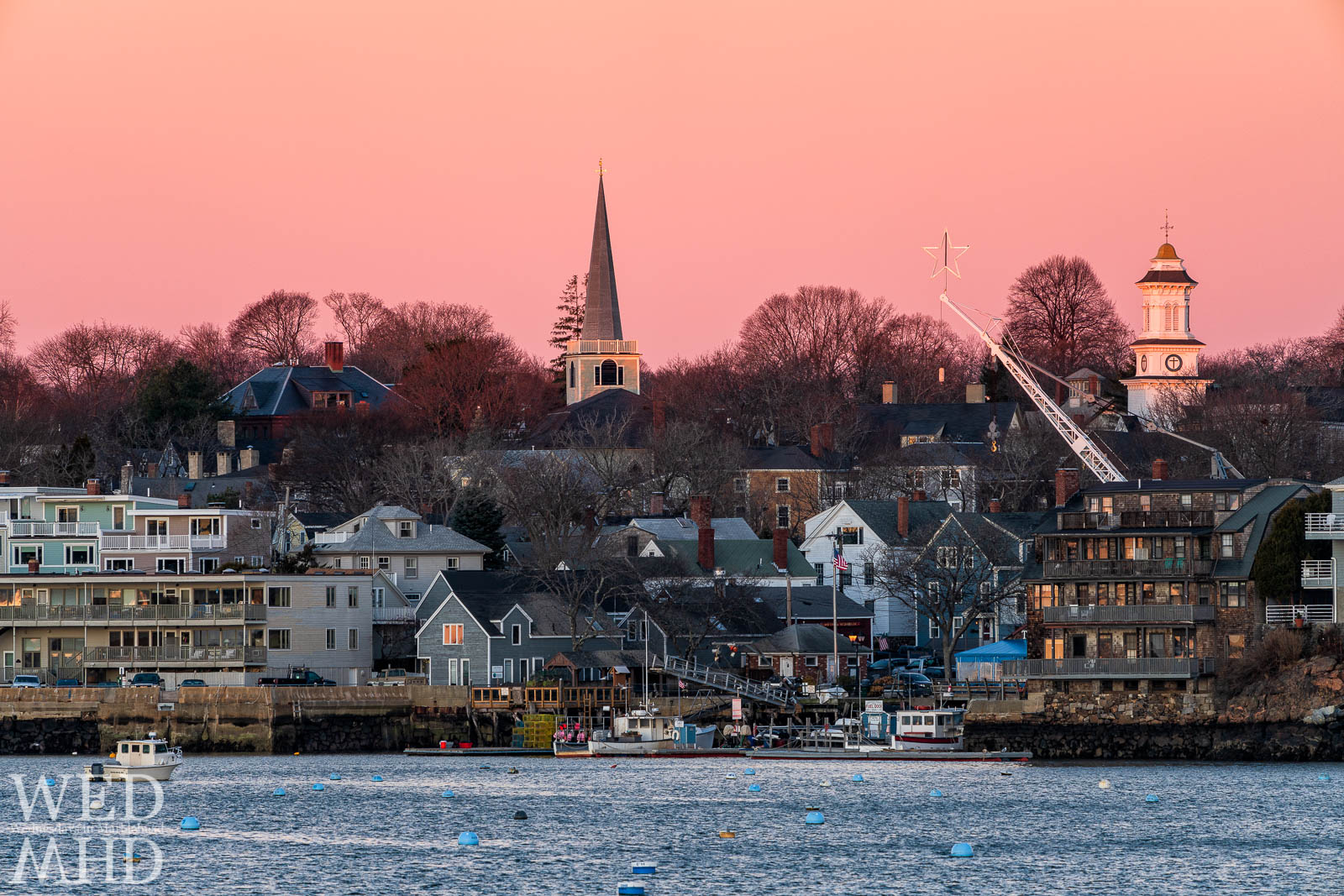 A glowing star stands between the St. Michaels and Grace Community Church steeples with the pink sky of morning forming a seamless backdrop