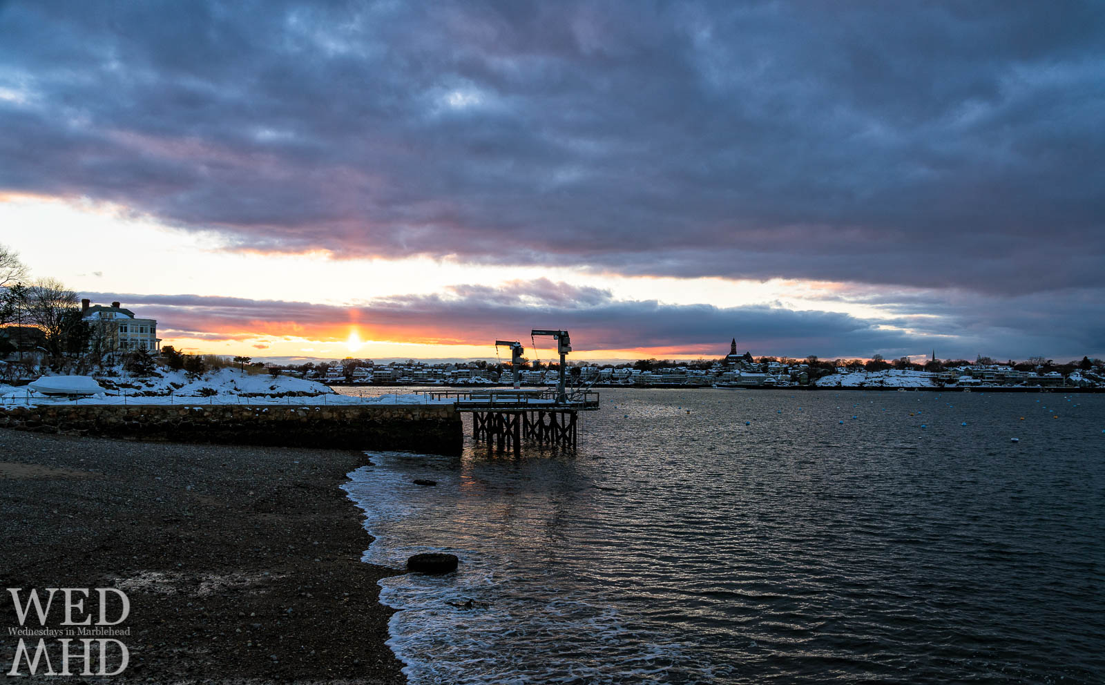 A sun pillar forms over Marblehead Harbor with the water coming ashore at low tide and the town blanketed in fresh snow