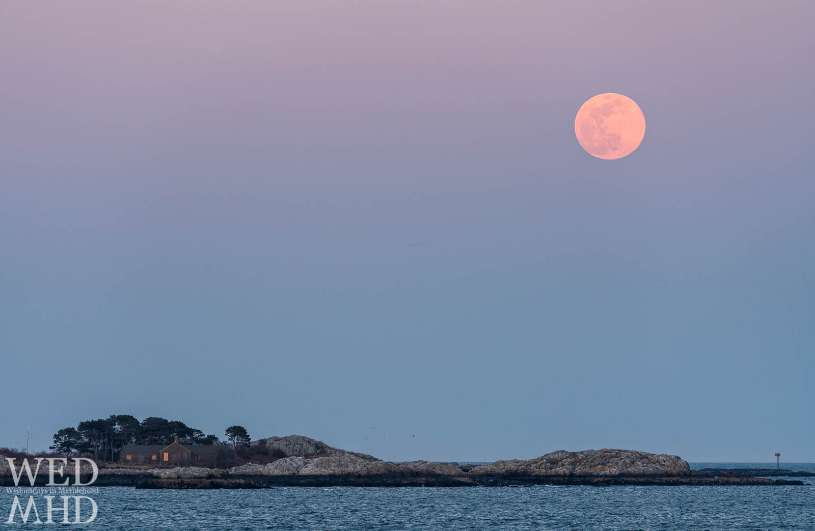 The super vernal worm moon rises over Childrens Island marking the first day of spring in Marblehead