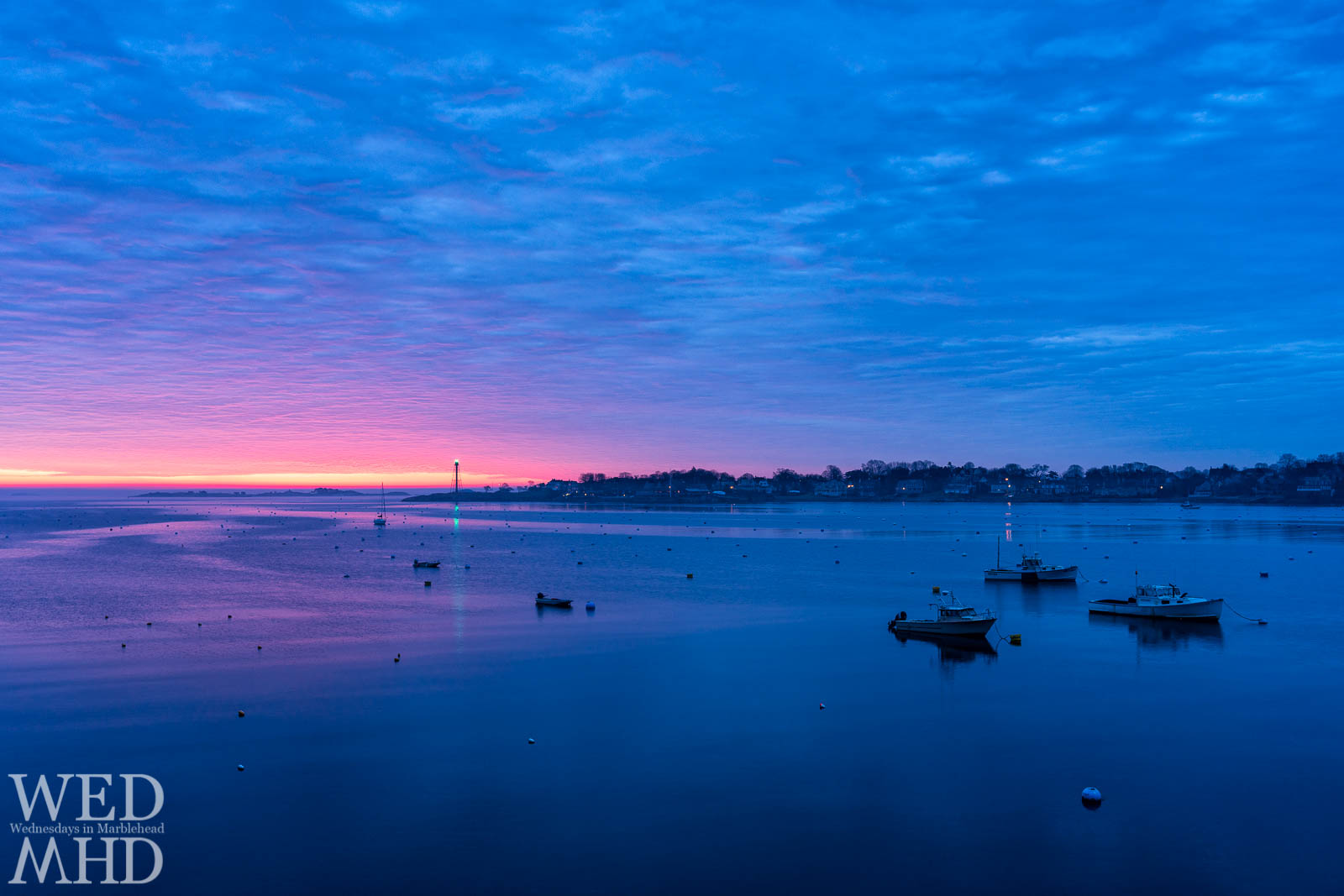 Dawn's colors break up the early morning blue hour on an empty harbor yet to fill with boats for the season