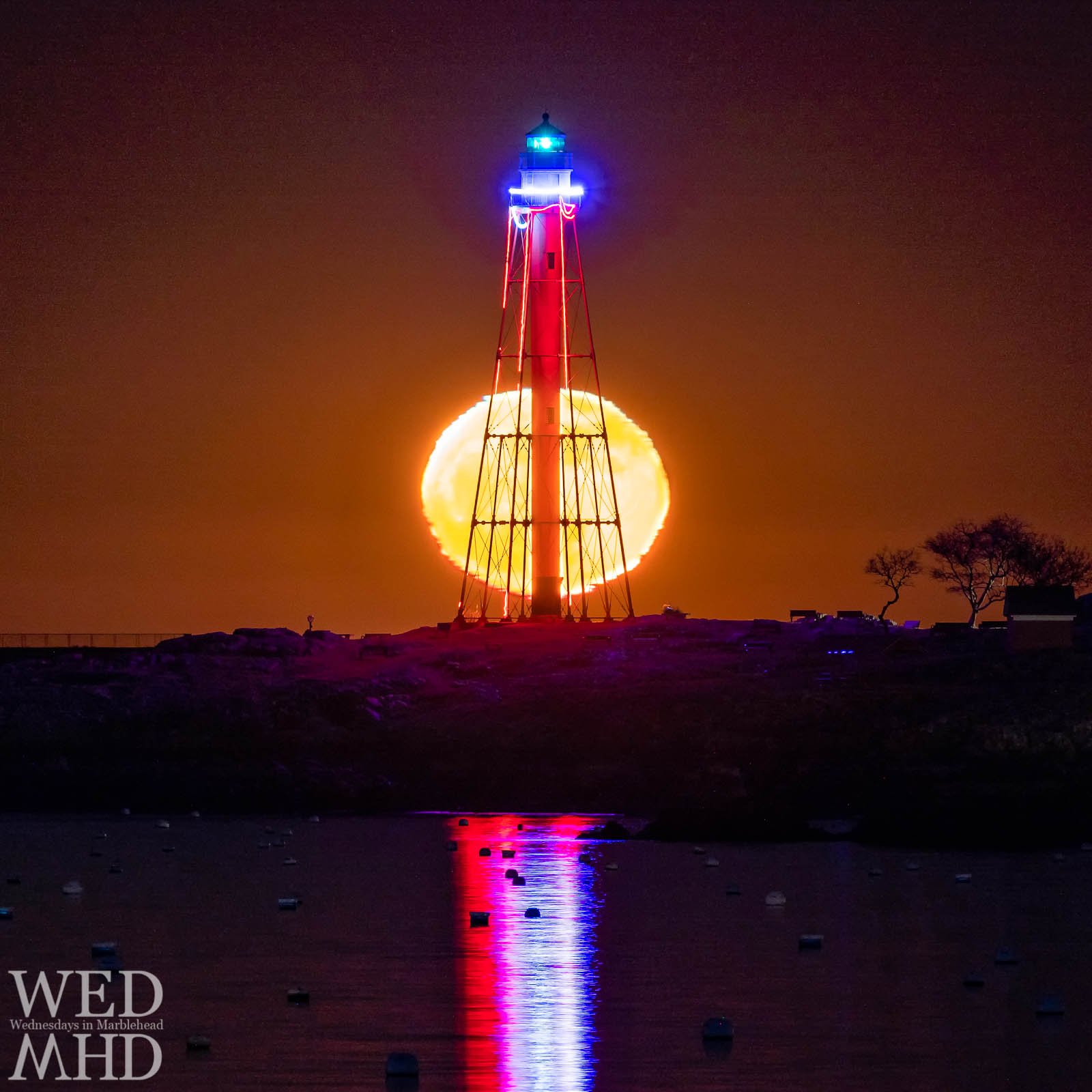 Marblehead light is backlit by moonglow in this long exposure image that captures the reflection of red, white and blue lights in the water below