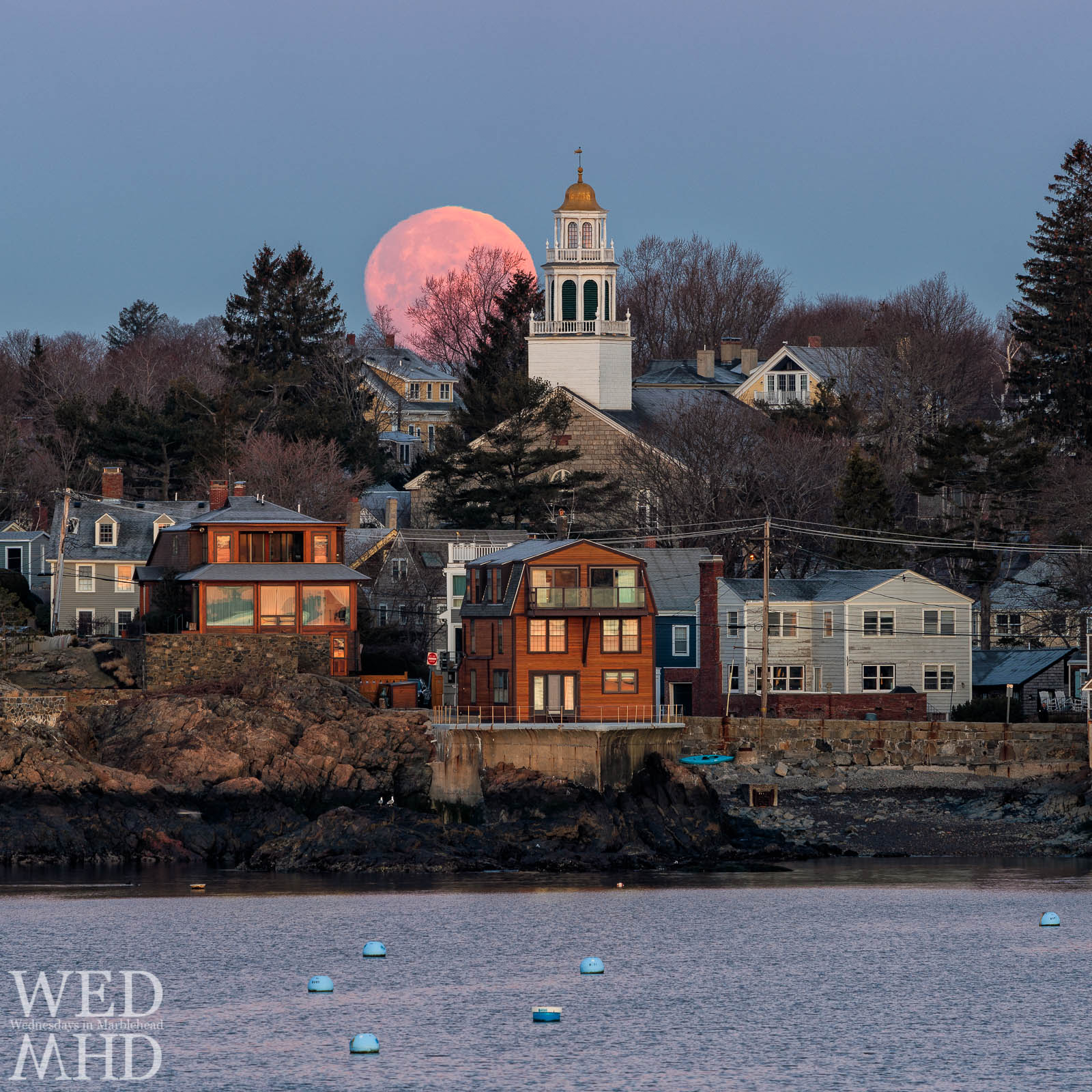 The full moon sets behind Old North Church in Marblehead on a late March morning wtih the sun's early light reflecting in the homes along the harbor
