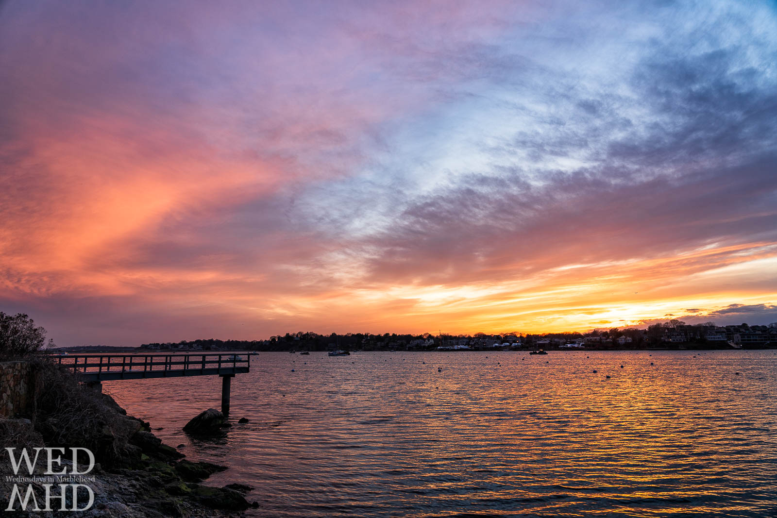 Spring sunsets take place over an empty Marblehead harbor as in this image from Parker Lane with a nearby pier surrounded by light