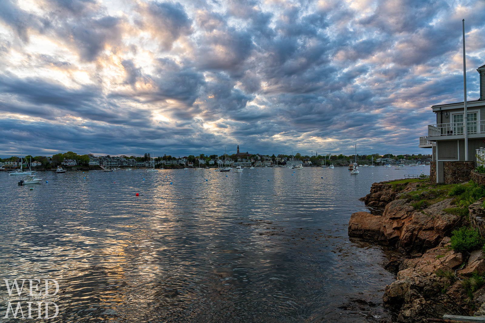 View of a cloudy evening at the end of Parker Lane features a home on a rocky outcropping and light reflecting in the water of Marblehead harbor