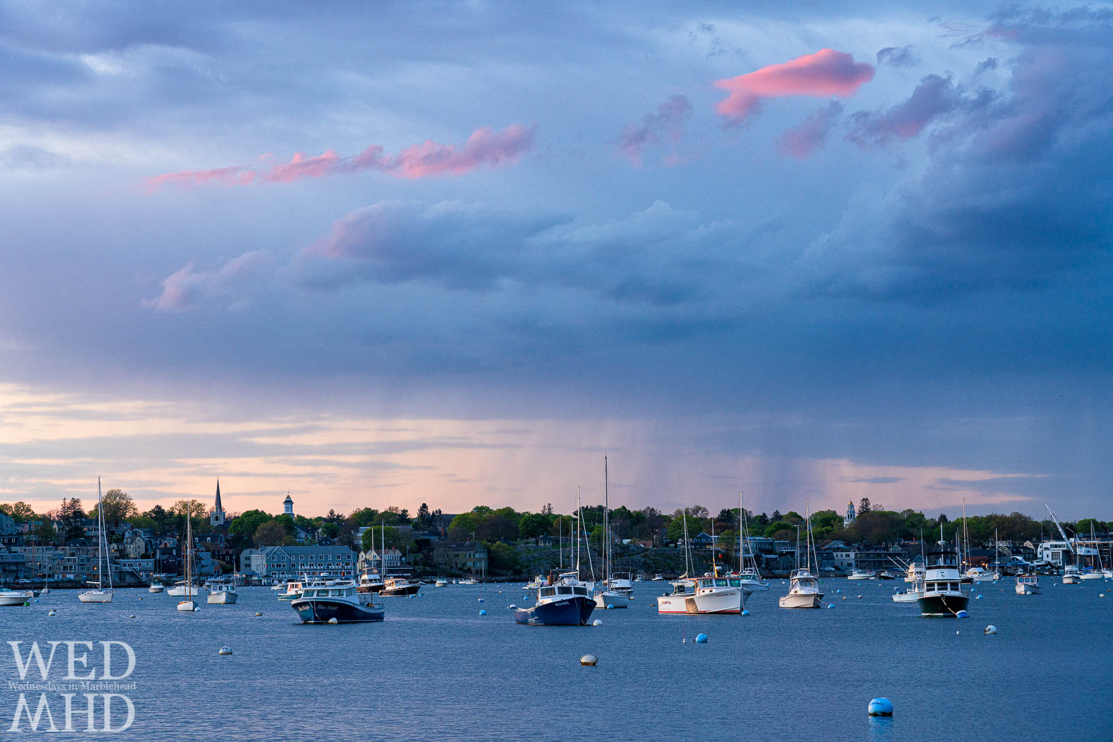 Rain clouds pass over Marblehead's mid-harbor resulting in pink clouds mixed with showers on a backdrop of familiar landmarks