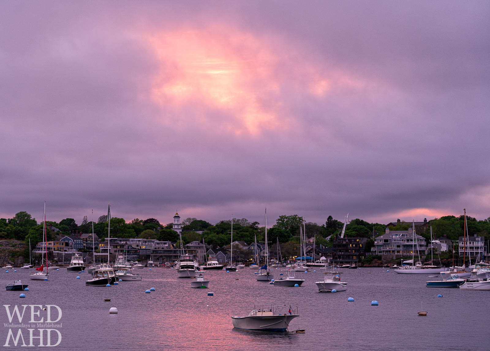 A boat is moored in the glow of an unusual sunset following a day of rain and grey clouds in Marblehead