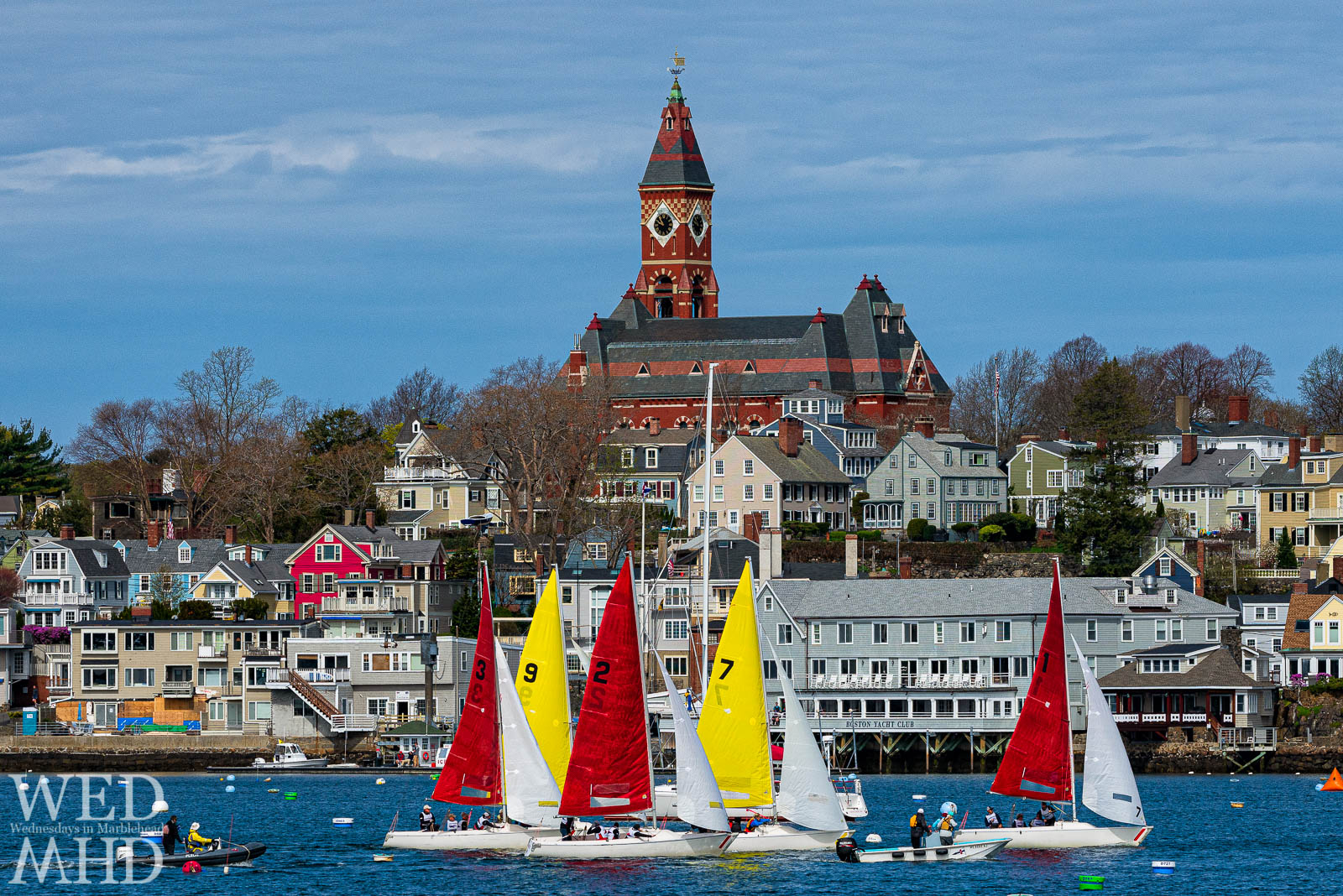 Boats with red and yellow sails compete for the Jackson Cup in front of Abbot Hall and the host Boston Yacht Club
