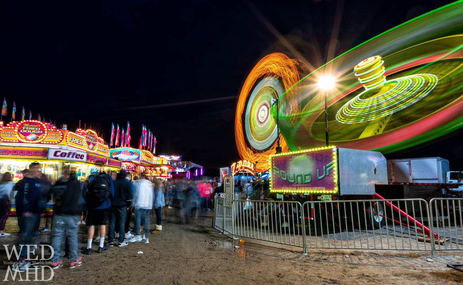 A long exposure image of the Marblehead Carnival creates spinning neon for the Round Up and Zipper rides and ghosts of the teenagers walking along the sand