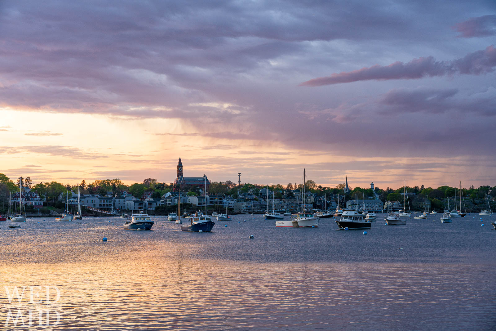 A spring sunset forms over Marblehead and a harbor filling with boats highlighted by green foliage and passing rain clouds