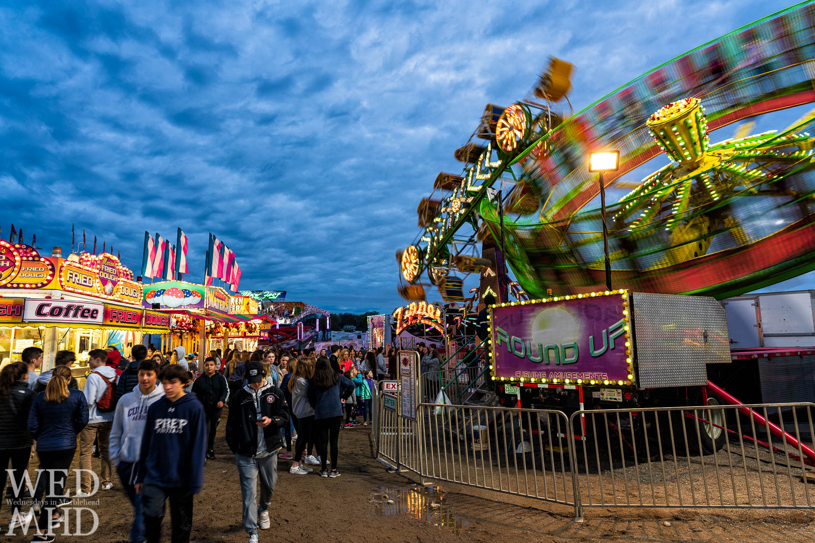 Teenagers walk the midway of the annual Marblehead High School carnival at Deveruex Beach with rides in full swing and food items calling out